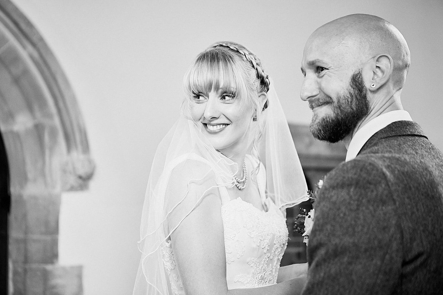A couple look back at their wedding guests on there wedding day at Gunby Hall