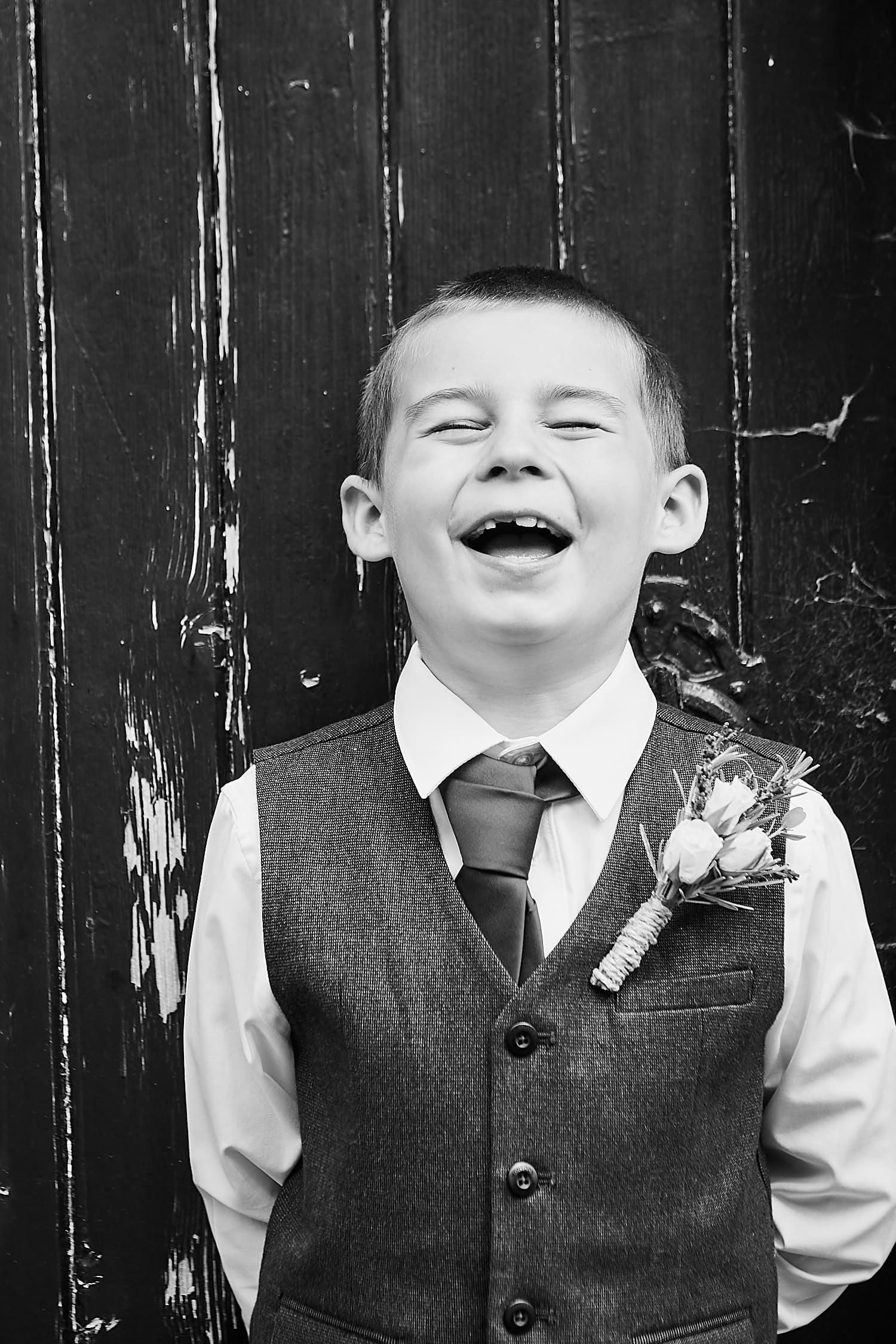 A page boy smiles and laughs against a black door