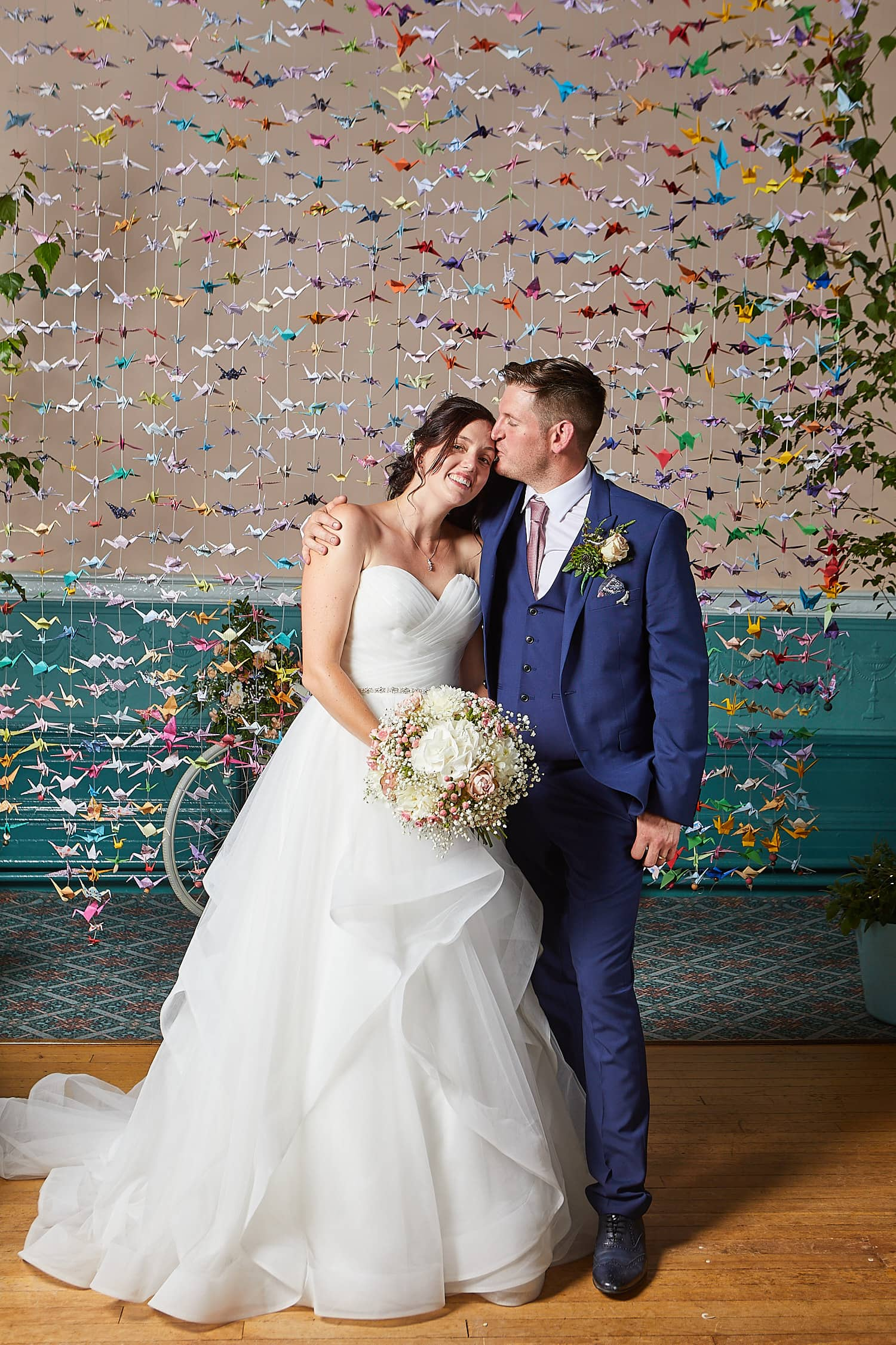 A couple kiss in front of a hand-made wedding backdrop