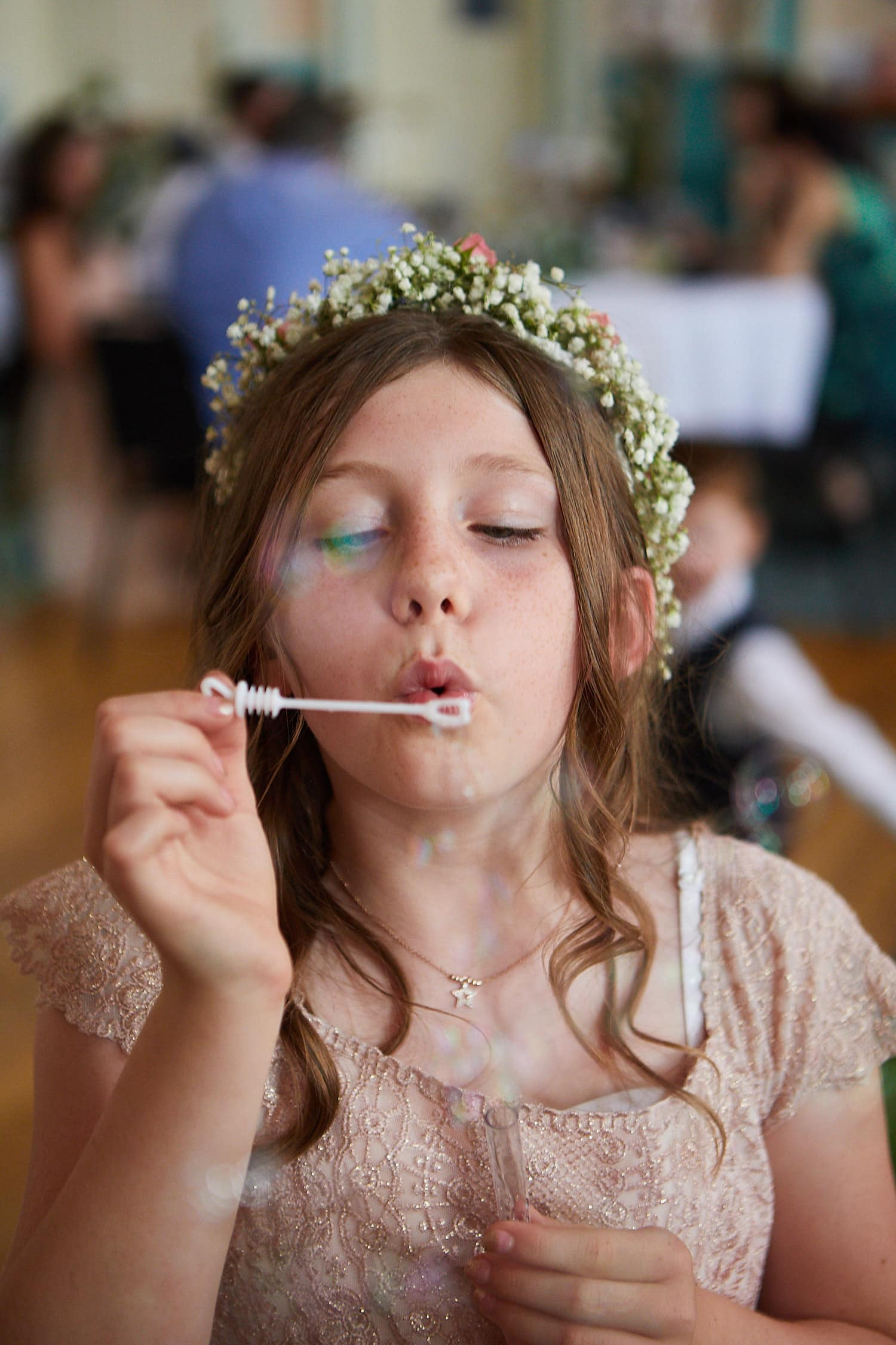 A flower girl blows bubbles at a wedding in Louth