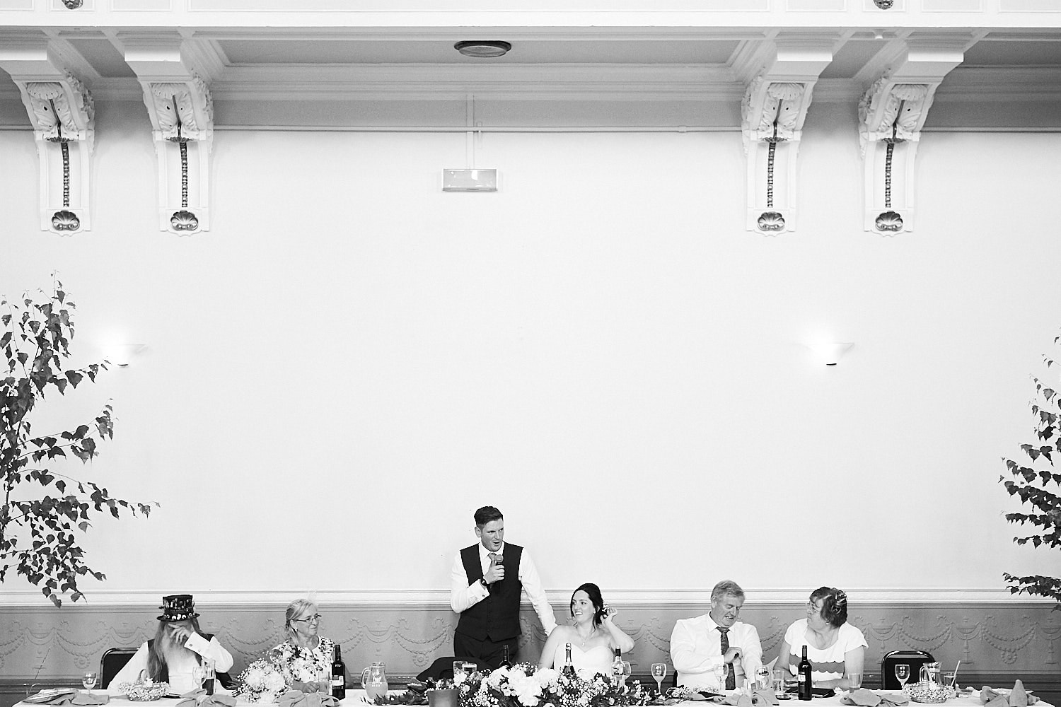 A groom gives a speech as both families sit either side of him