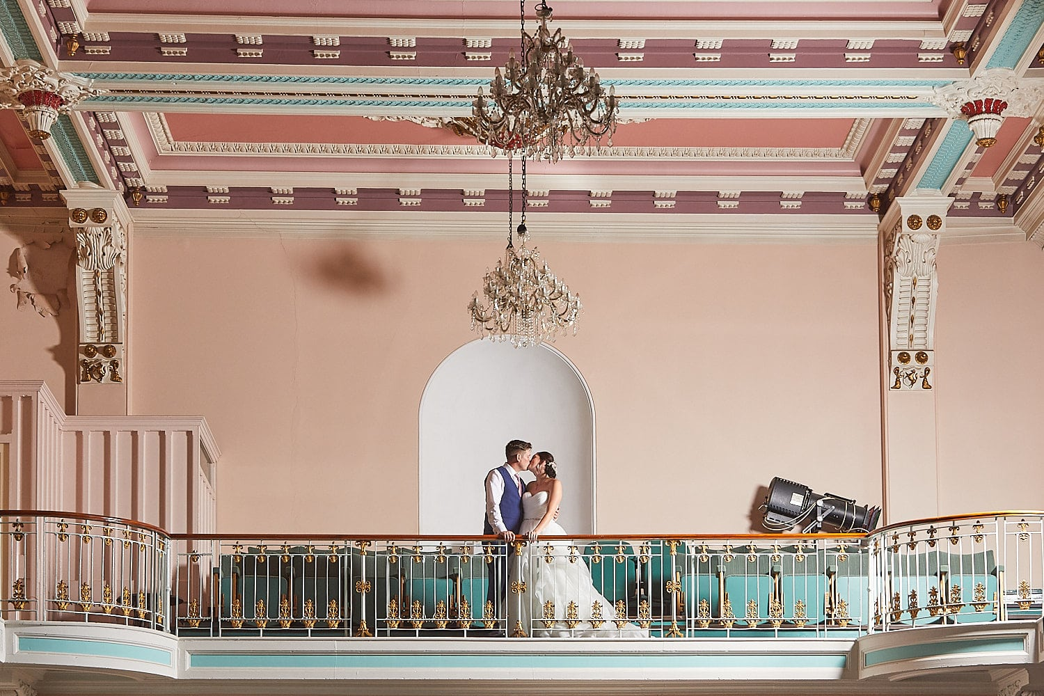 A couple kiss on the balcony of Louth Town Hall on their wedding day in Lincolnshire