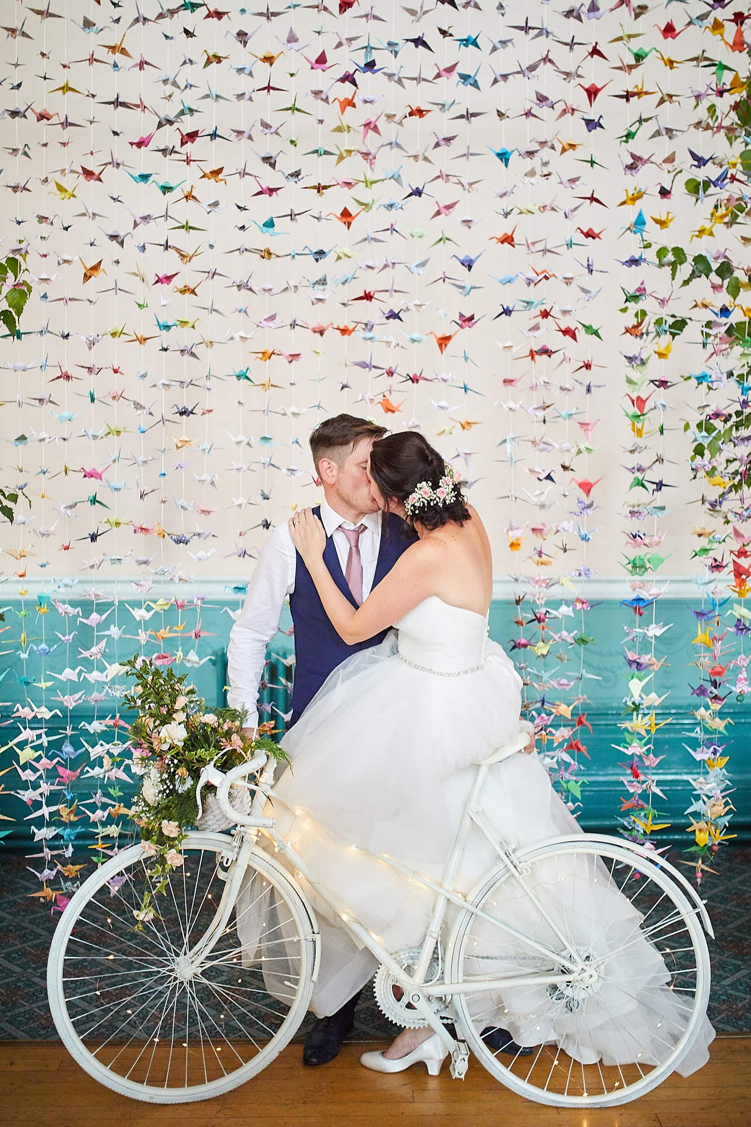 A couple kiss in front of their wedding backdrop