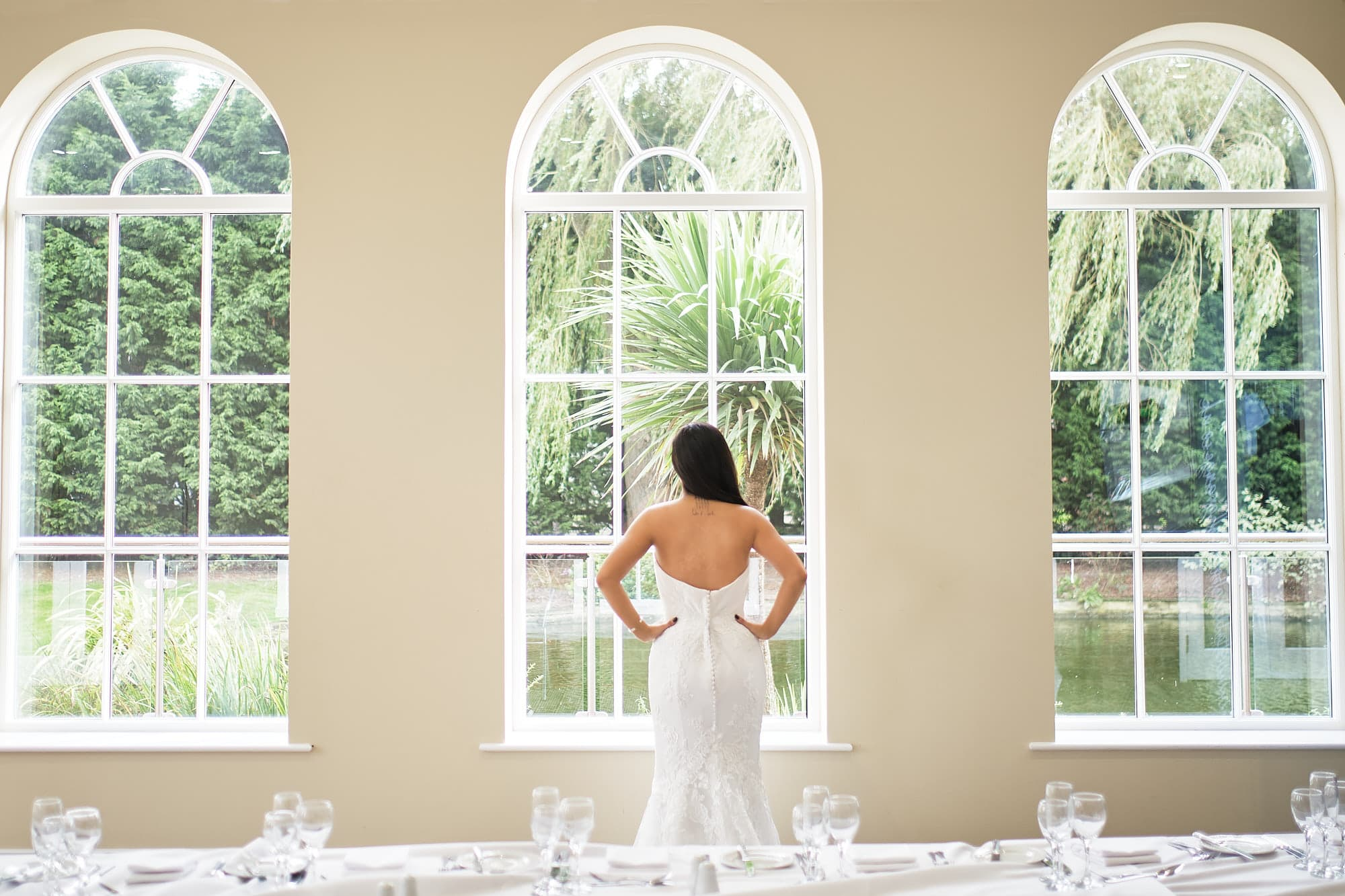 A bride looks out of the windows onto the gardens at Lincolnshire wedding venue Stallingborough Grange.