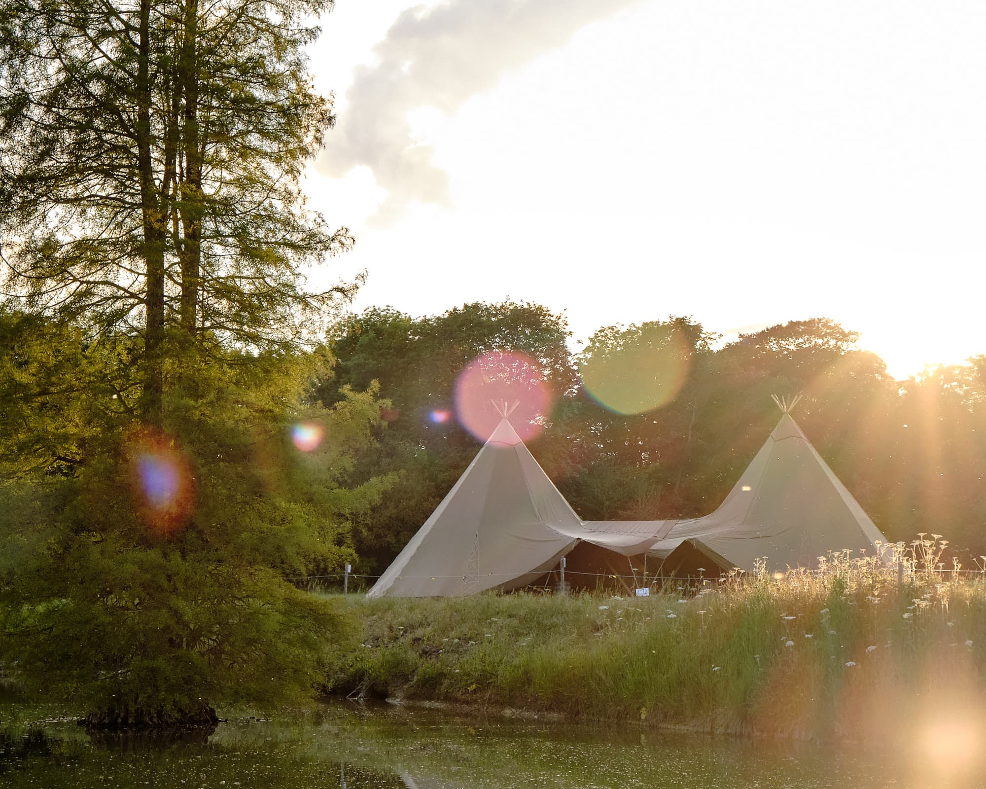 A tipi Lincolnshire Wedding at Revesby Estate. The tipi is located in front of the lake at sunset and a sun flare enters the camera
