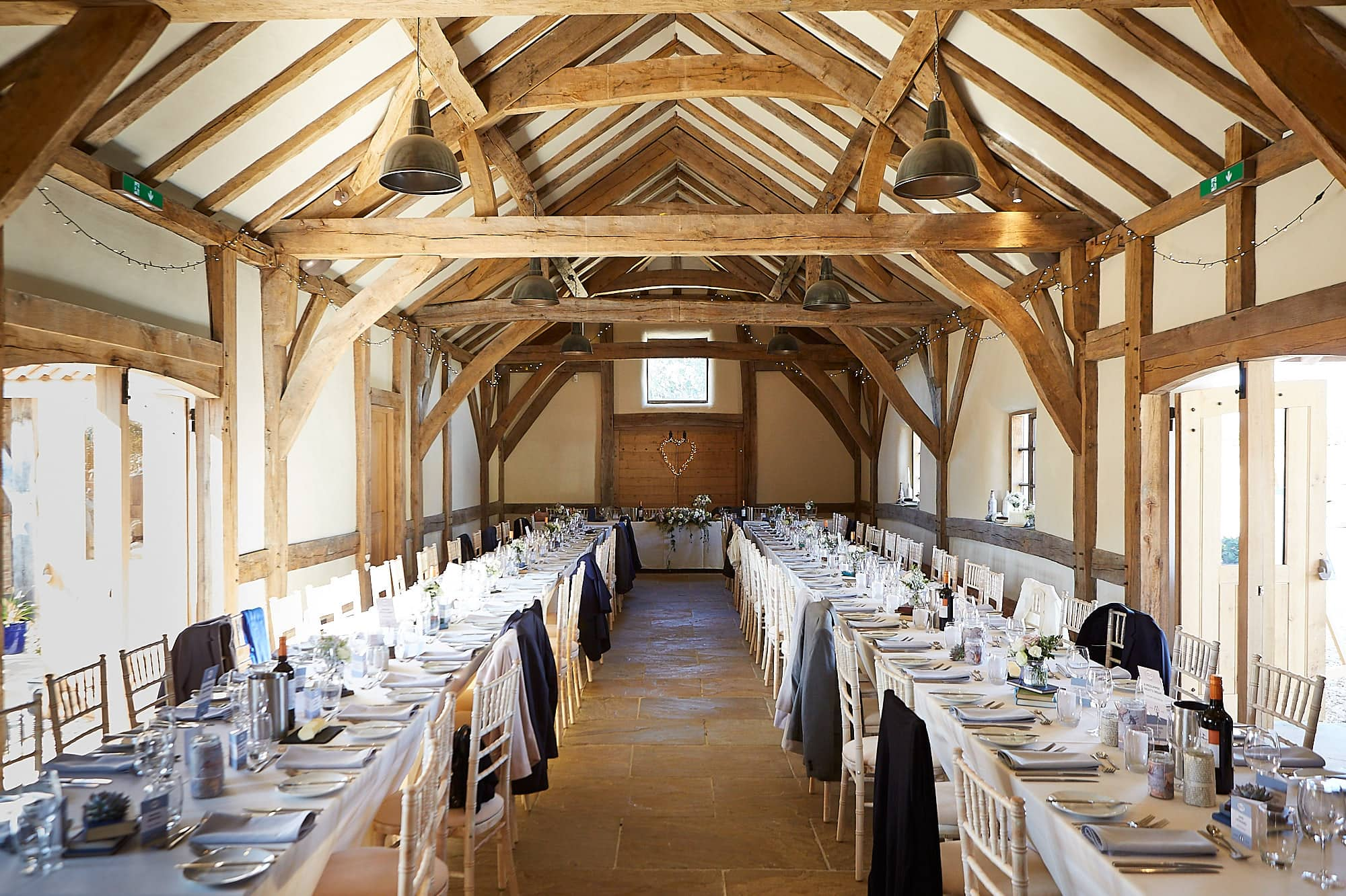 The interior of the main barn at Abbey Farm Weddings. The tables are laid and coats sit on the back of chairs as people enjoy the sunshine outdoors.