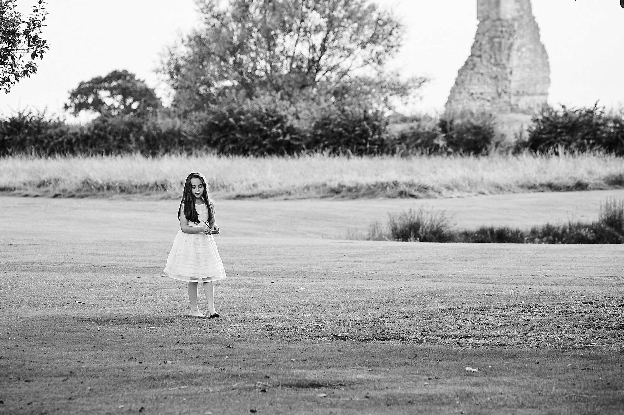 A girl plays outdoor on grassland near the ruins of Kirkstead Abbey on a wedding day.