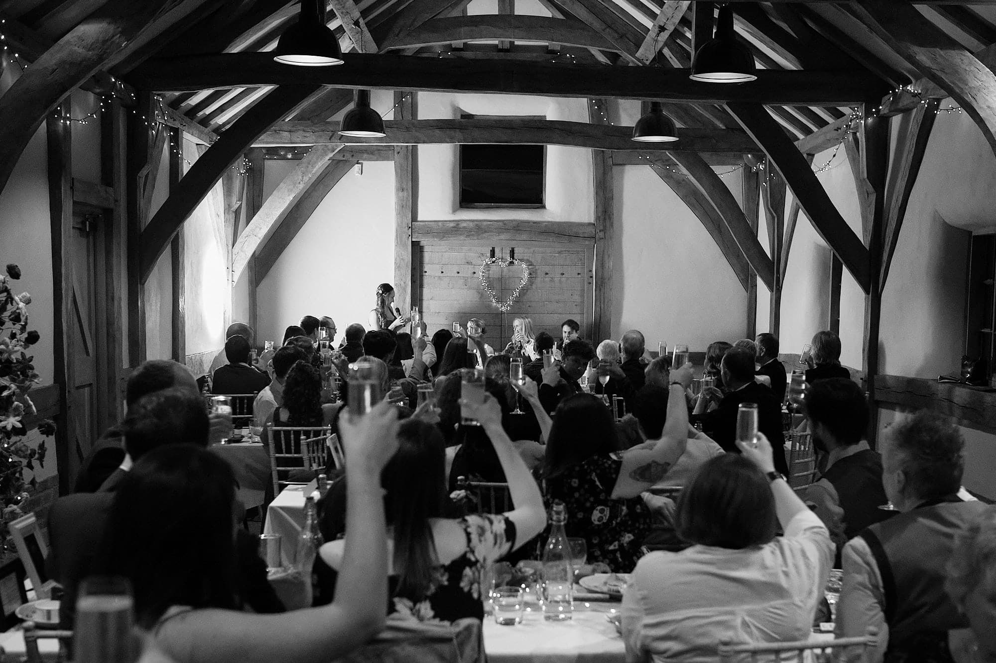 Possibly the best barn wedding venue in Lincolnshire Abbey Farm. This black and white photograph shows guests toasting a gay couple on their wedding day.
