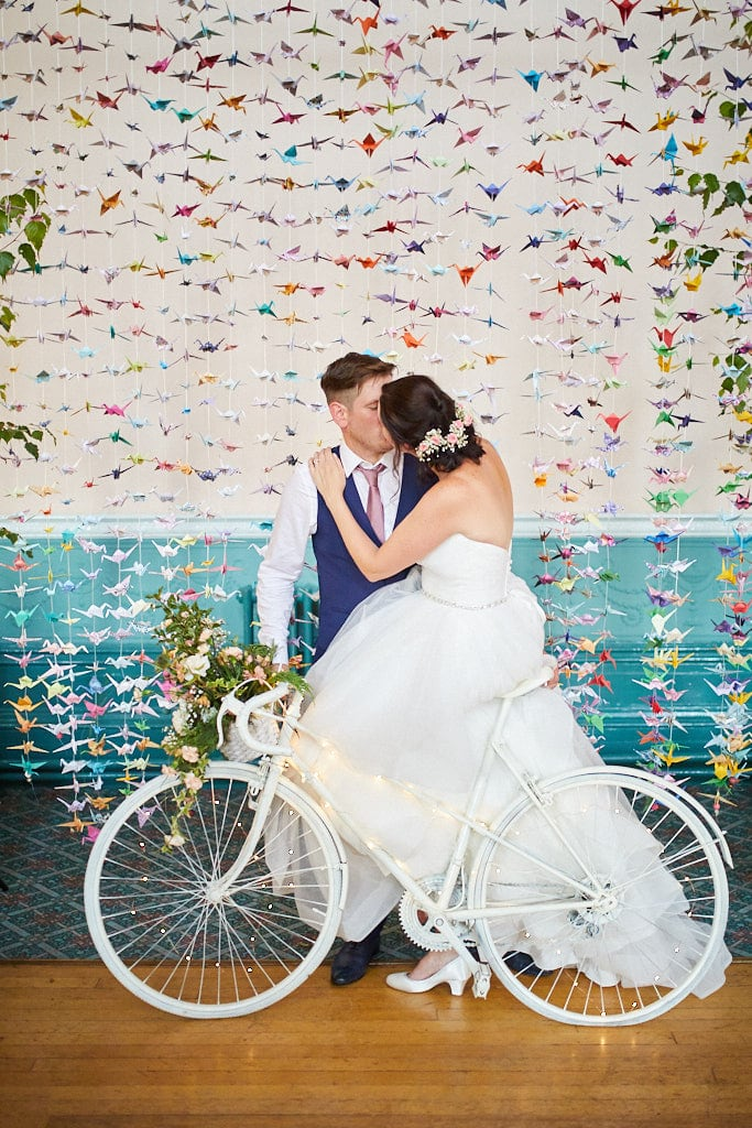 A couple kiss on a white vintage racing bike in front of a backdrop of paper cranes on their wedding day in Louth, Lincolnshire