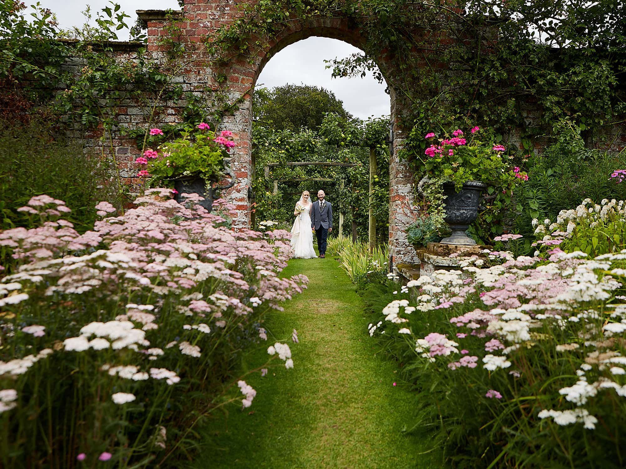 A couple walk through the gradens of National Trust wedding venue Gunby Hall in Lincolnshire. Th couple walk through an arch with flowers blooming in the garden.