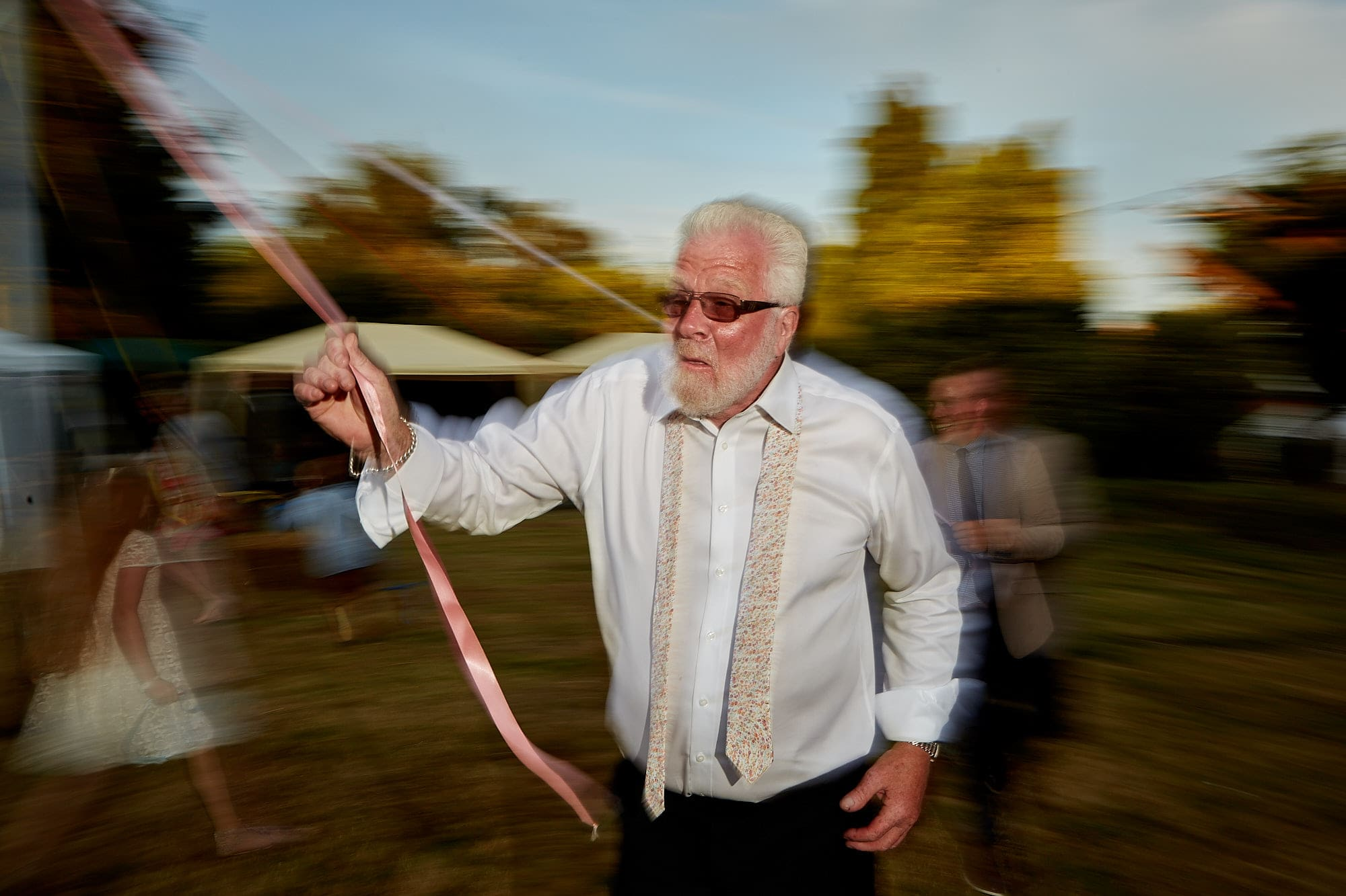 A man rushing round a maypole enjoying himself on his daughters wedding day in Lincolnshire.