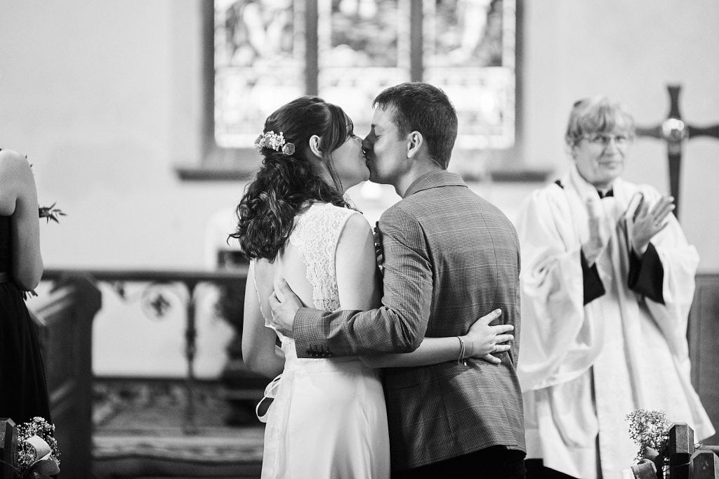 A couple kiss as they celebrate getting married. the vicar, out of focus, looks on from the background, string at the camera.