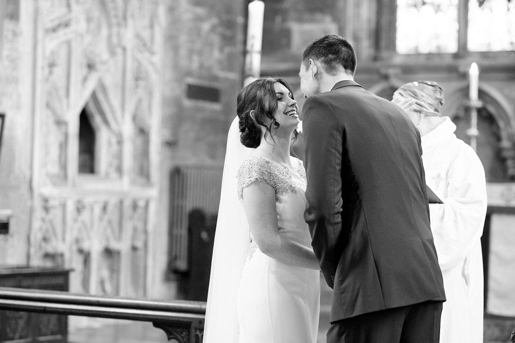 A couple kiss for the first time as husband and wife. in the background, the vicar averts her eyes.