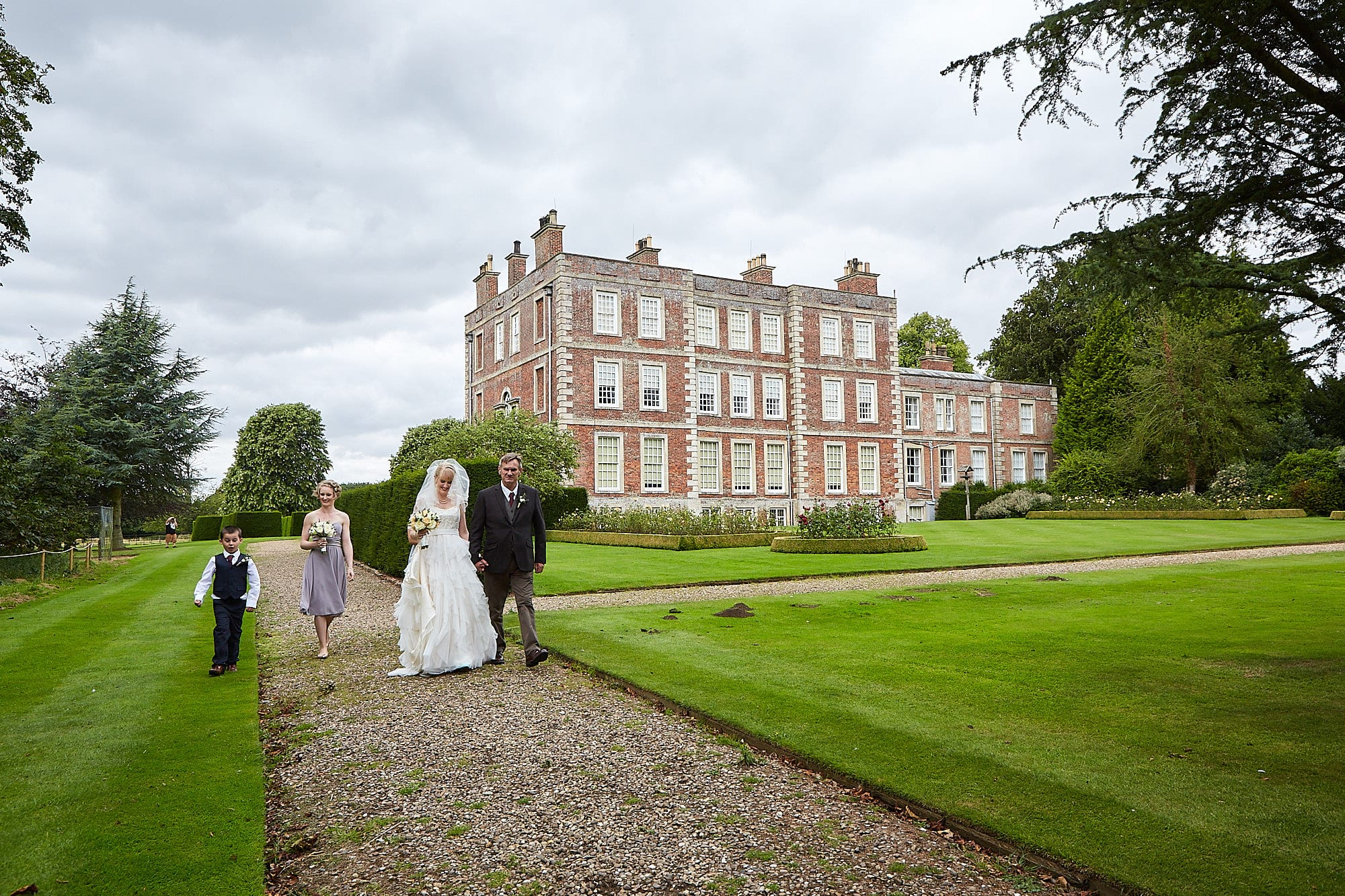 father, bridesmaid and page boy walk a bride to the church at Gunby Hall, National Trust wedding venue in Lincolnshire.