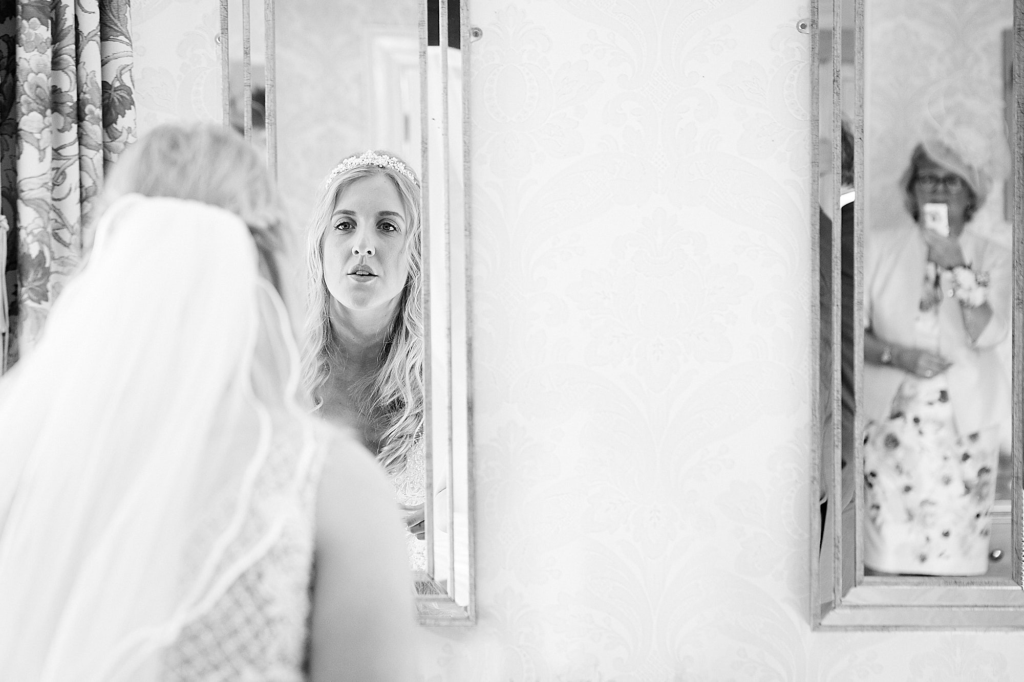 A documentary wedding photograph of a bride preparing her makeup in the mirror. In the reflection, her mother proudly looks on and snaps a photo on her phone.