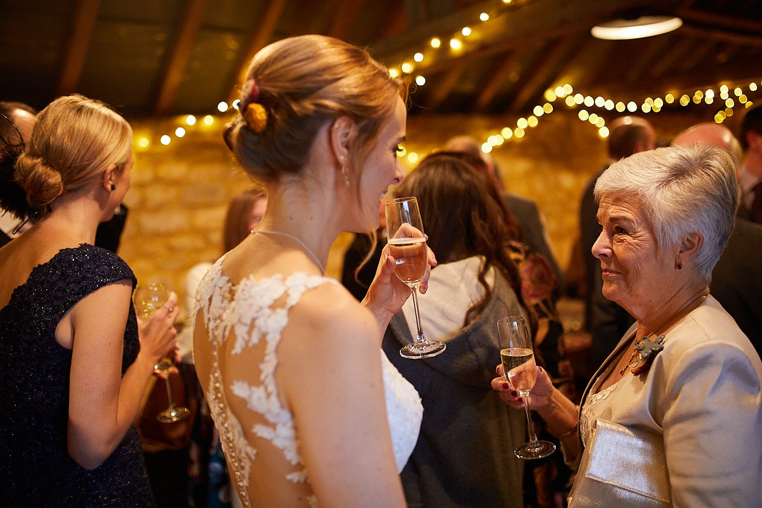 A bride chats with her mother who looks on proudly