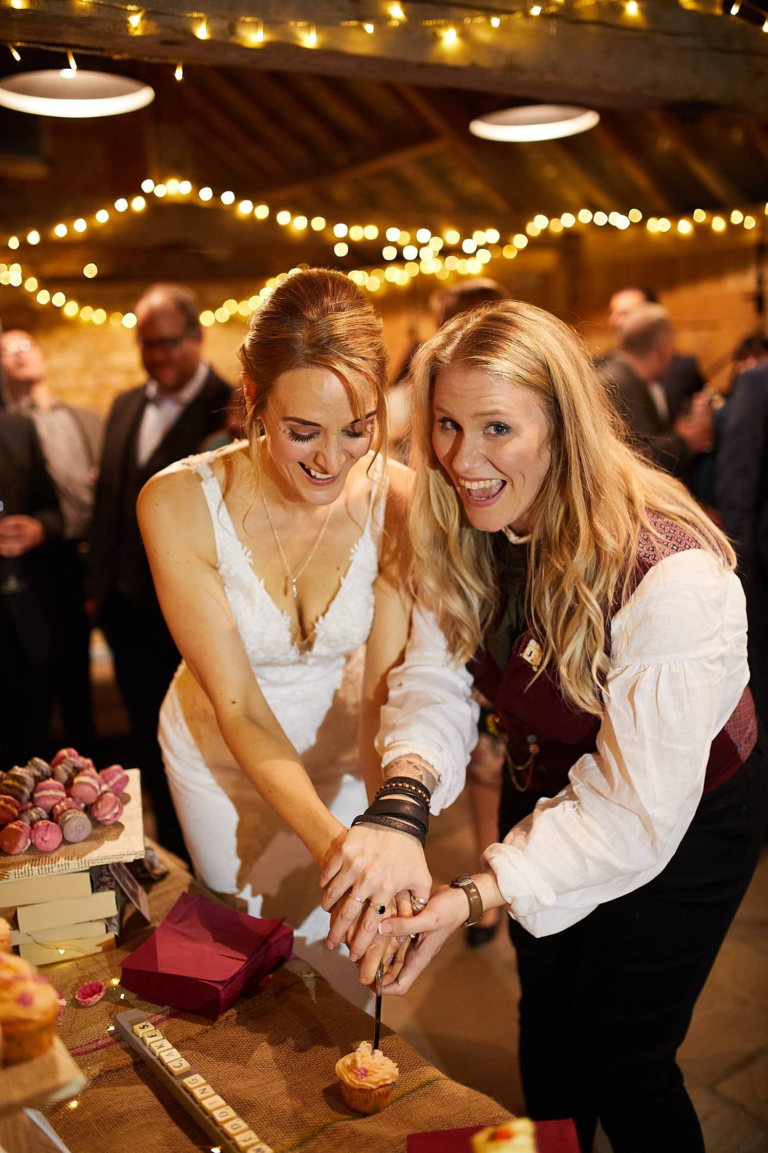 A couple cut a small cupcake at their Woodhall Spa wedding