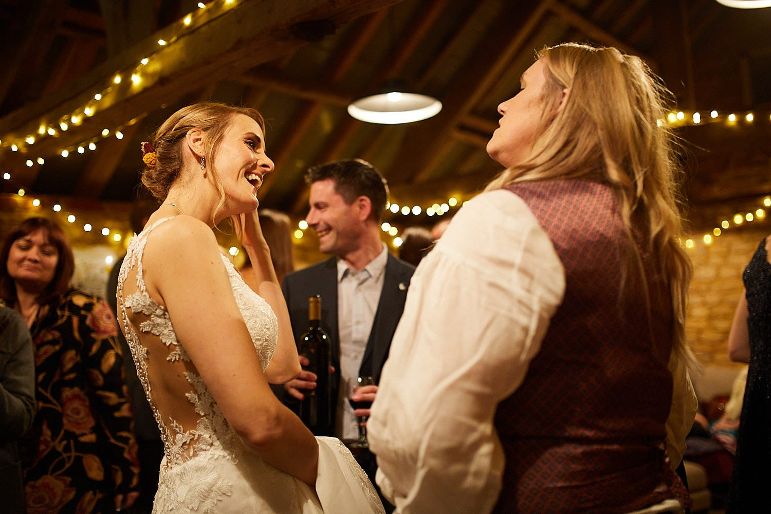 A newlywed couple laugh as they chat with each other