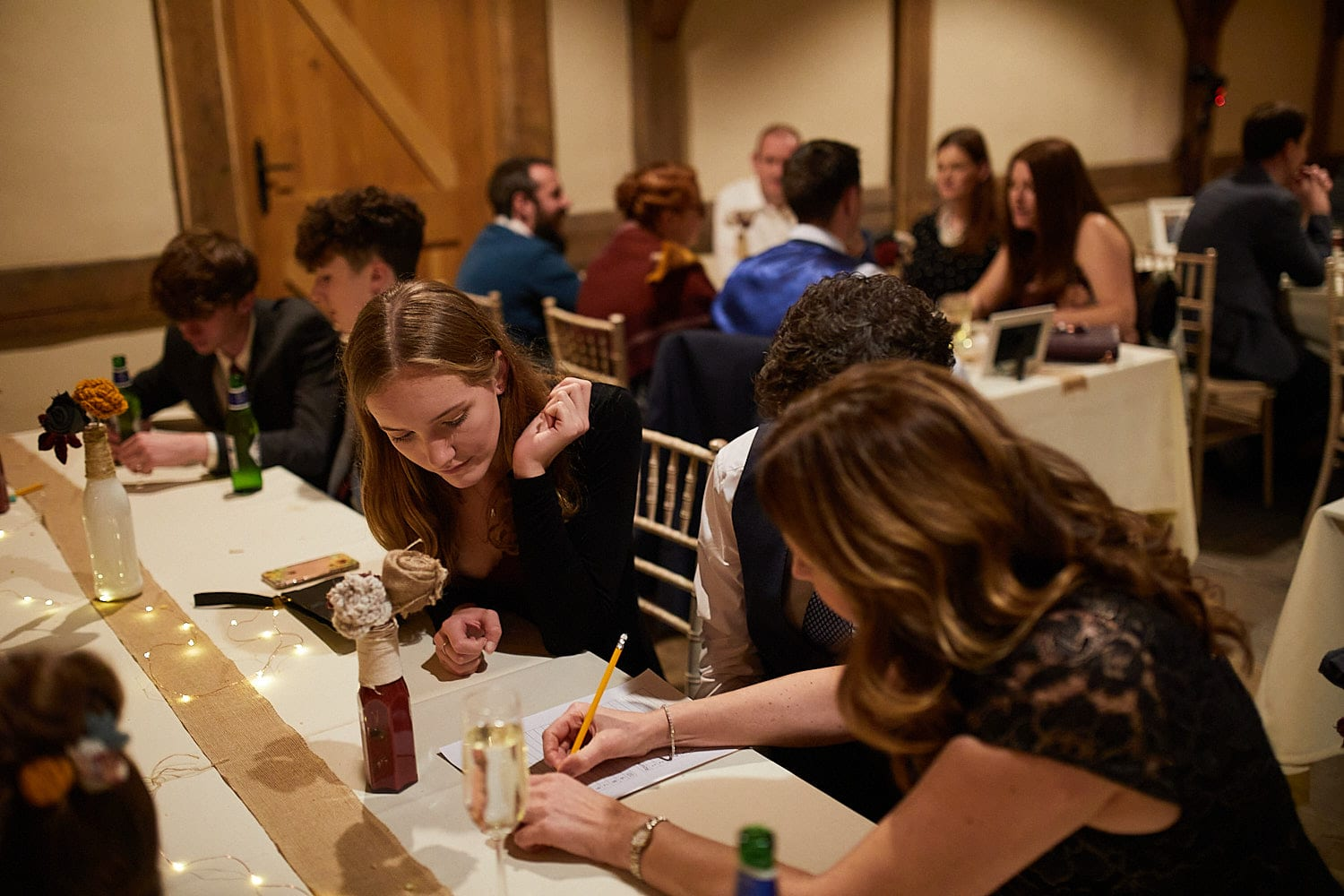 Friends eagerly confer at a wedding quiz