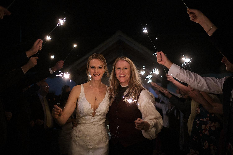 A couple leave Abbey Farm through sparklers