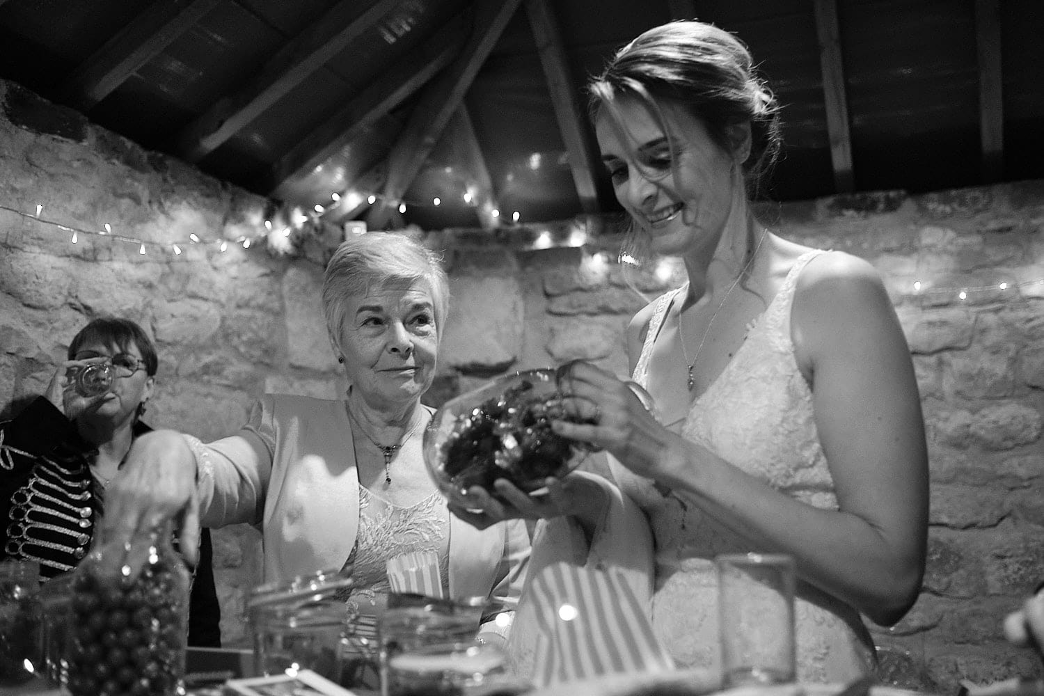 A mother gives a loving look to her daughter as the gather sweets on her wedding day