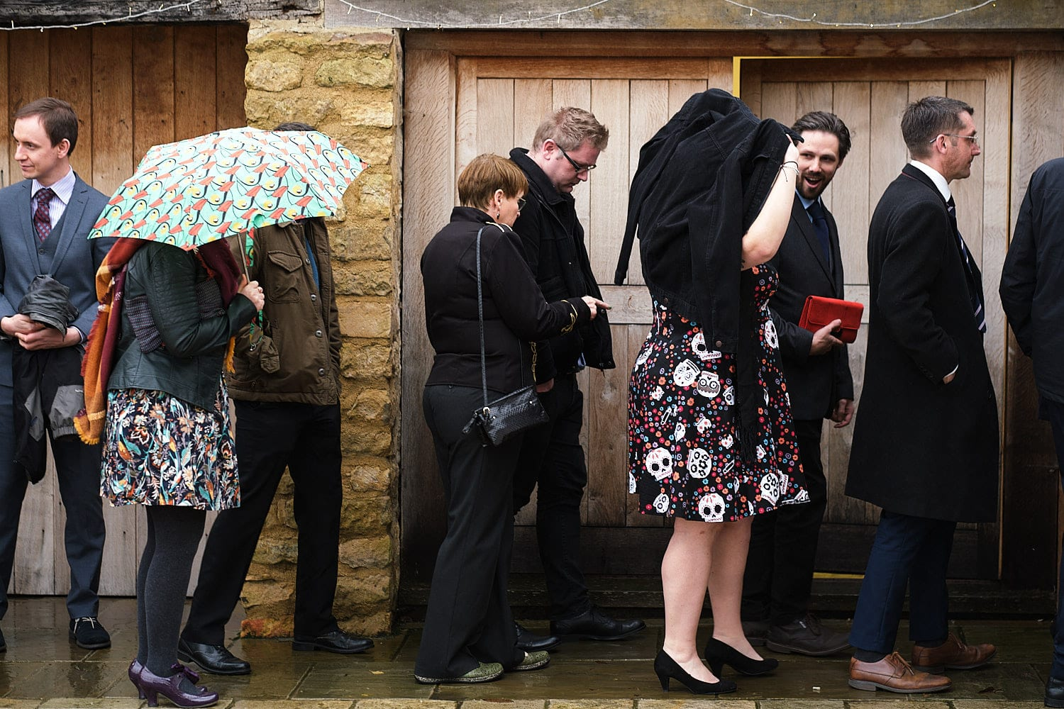 wedding guests cover themselves with coats and umbrellas on a wet wedding day