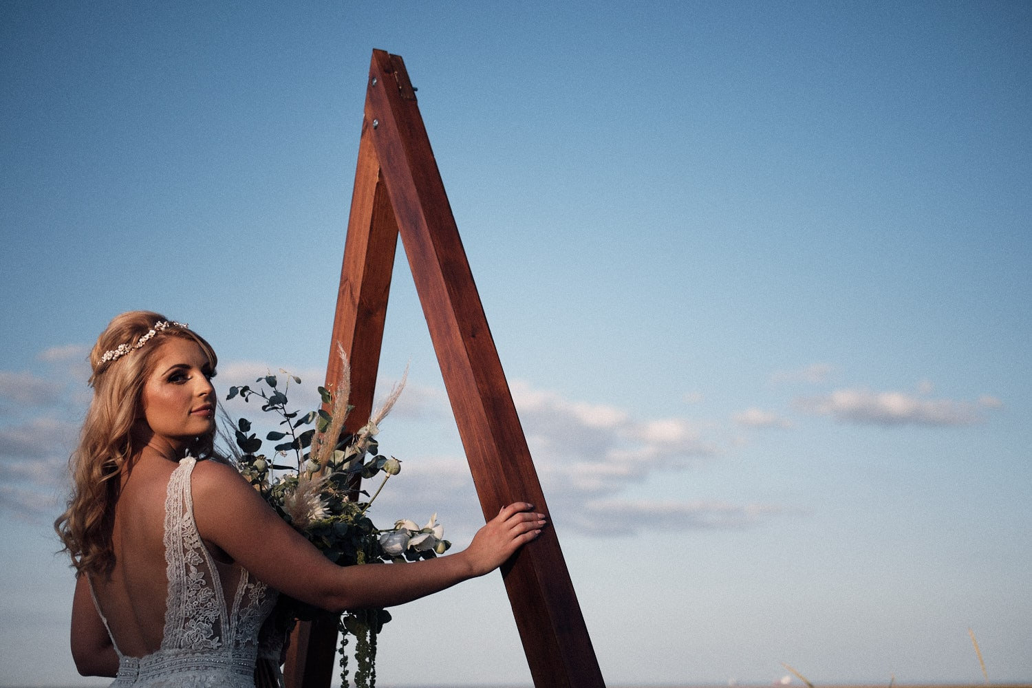 A bride poses against a wooden backdrop with a clear blue sky behind her