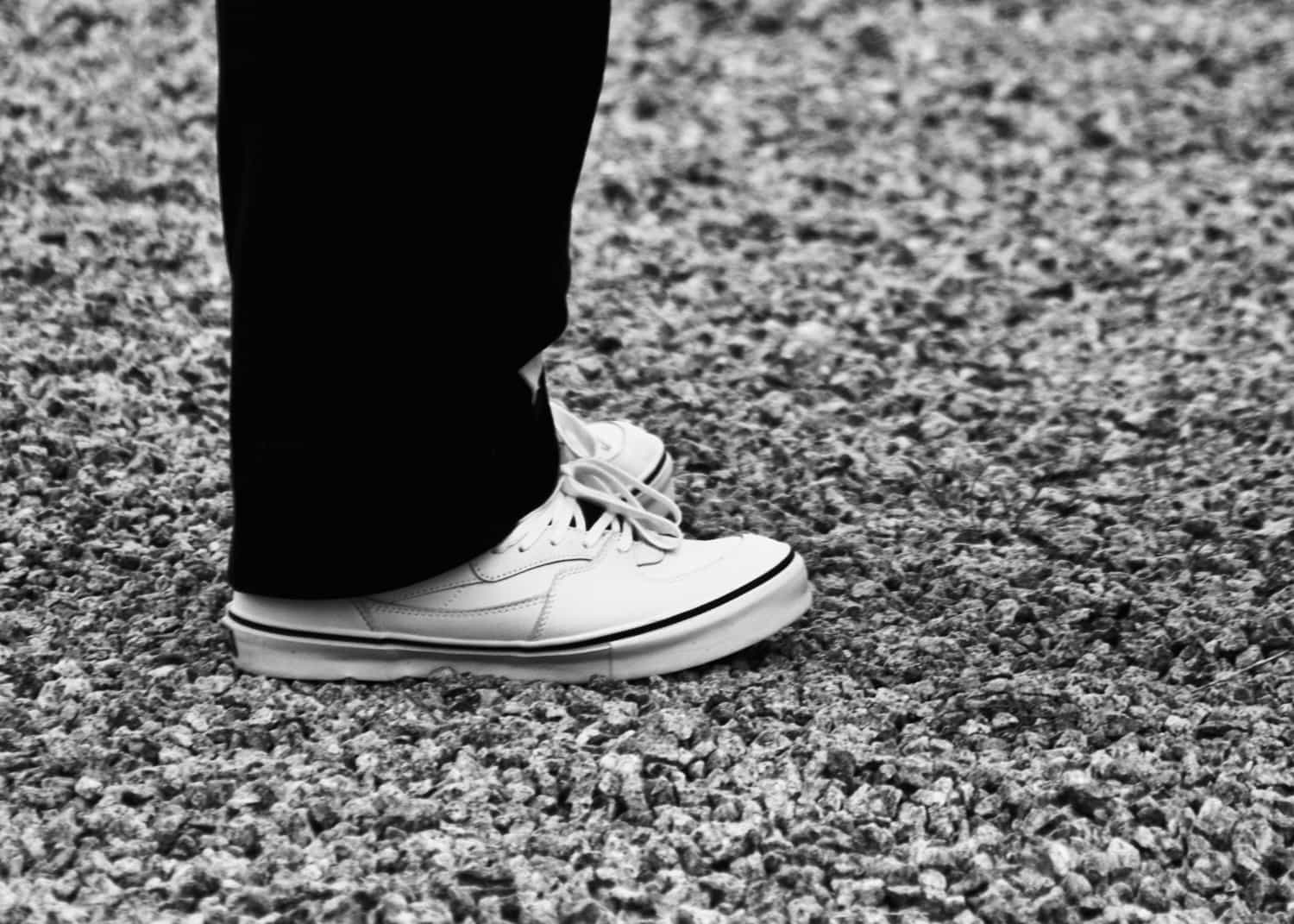 Black and white photo of a grooms feet with Half Cabs Vans trainers on them