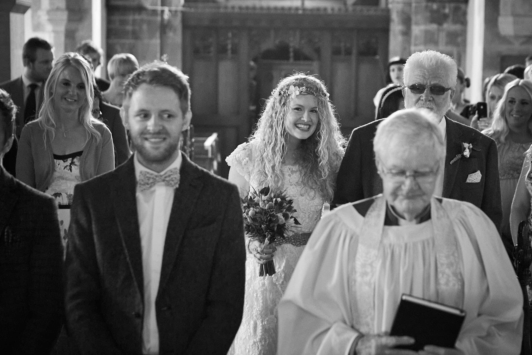 A nervous groom senses his wife to be approach the front of the church, she peaks to see if she can see his face.