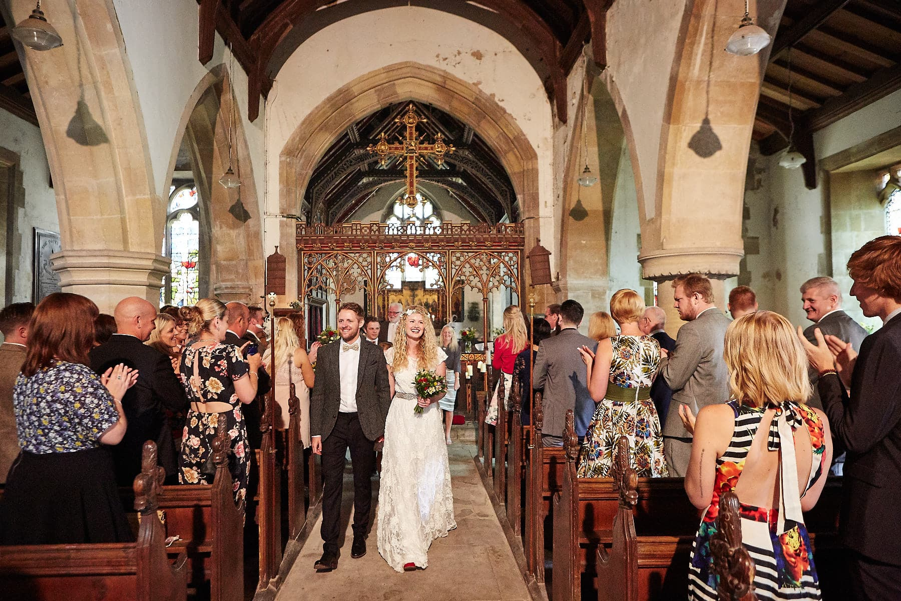 A couple smile and wave to friends as they leave the church on their wedding day in Lincolnshire.