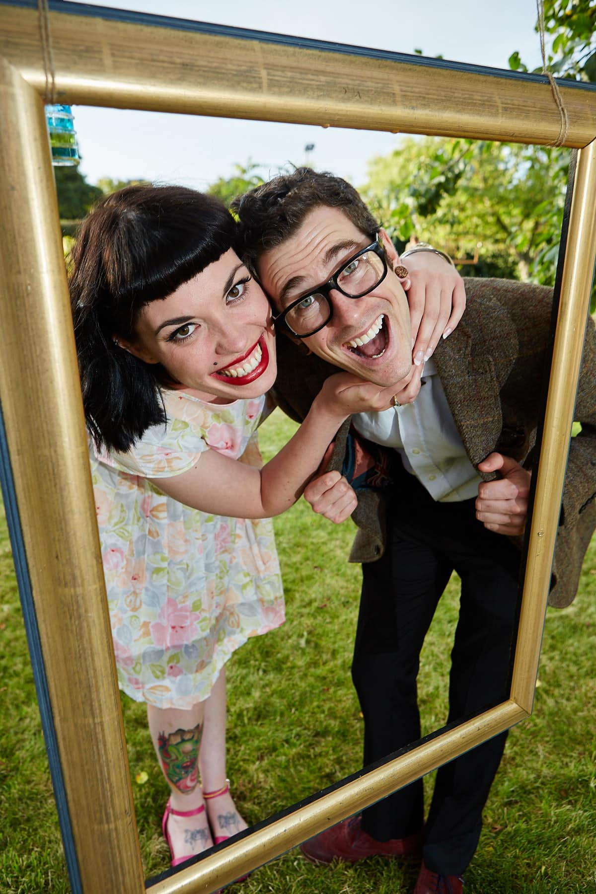A couple pose in picture frames at a Lincolnshire wedding