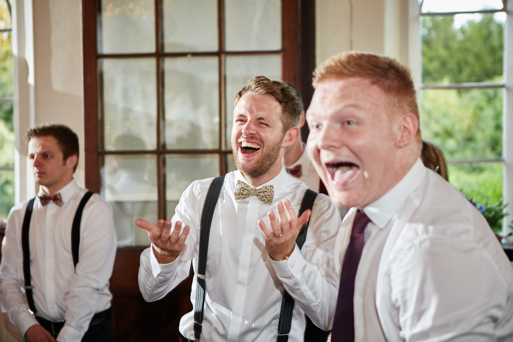 A groom and his friends laugh during his wedding reception.