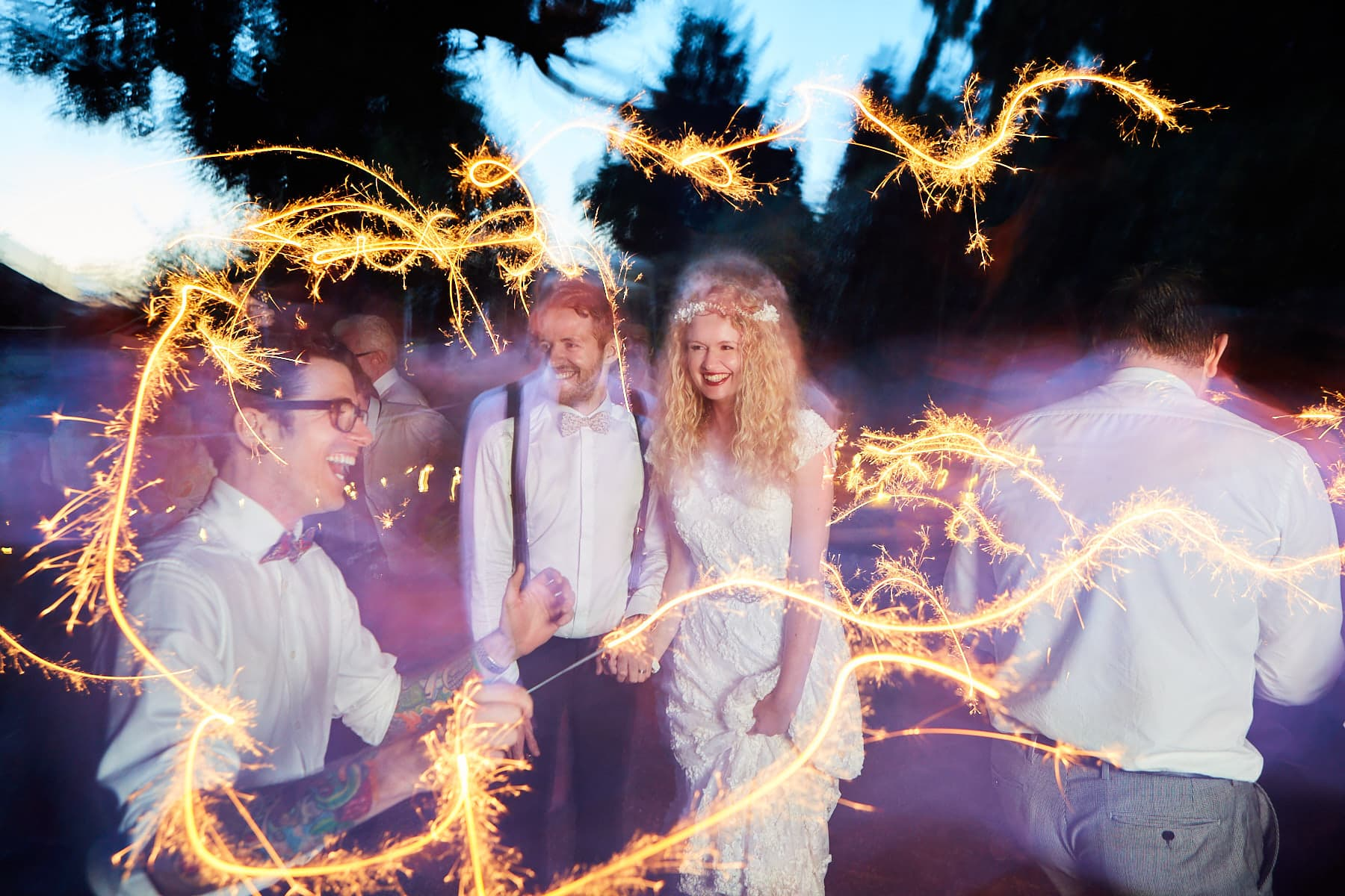 A couple pose whilst their friends dance around them with sparklers on their wedding day.