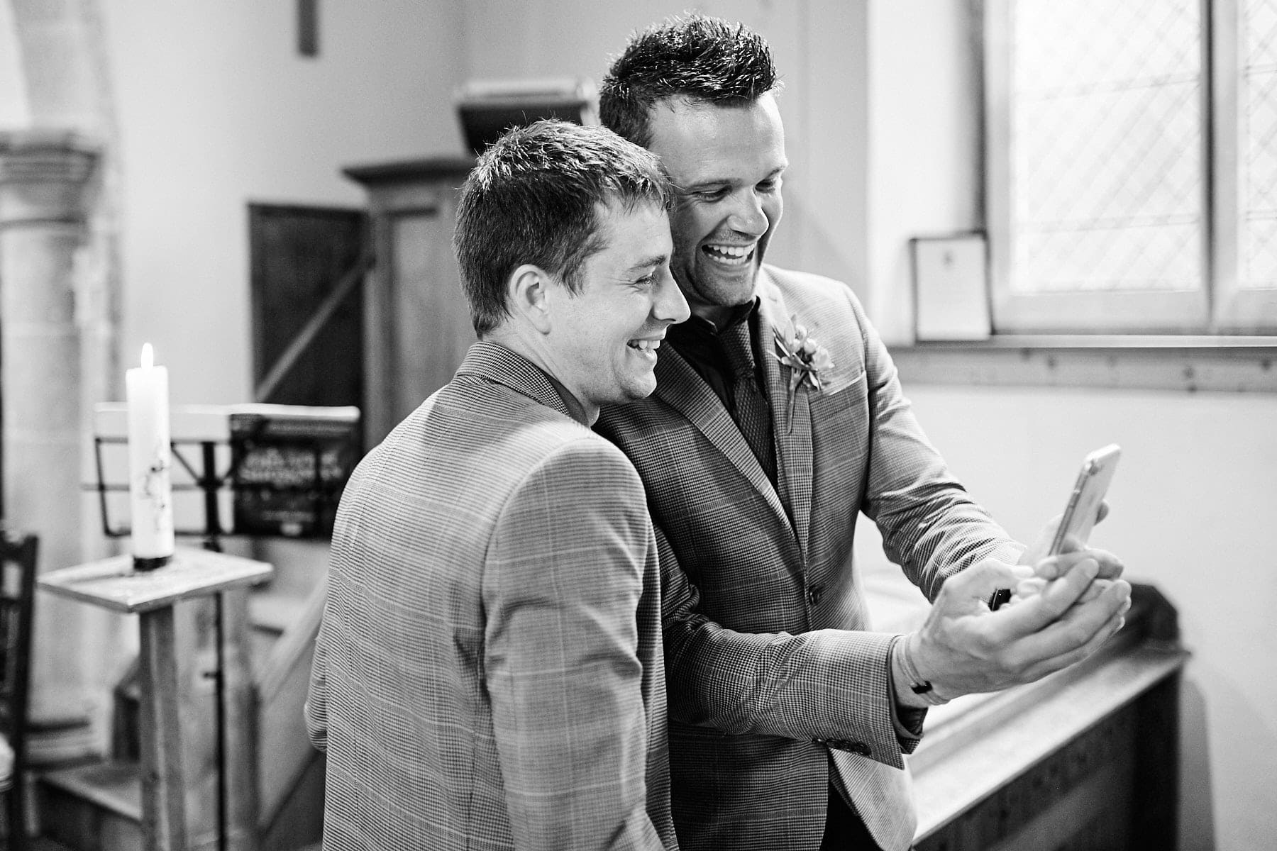 A groom and his best man pose for a selfie as they wait in church for the bride.
