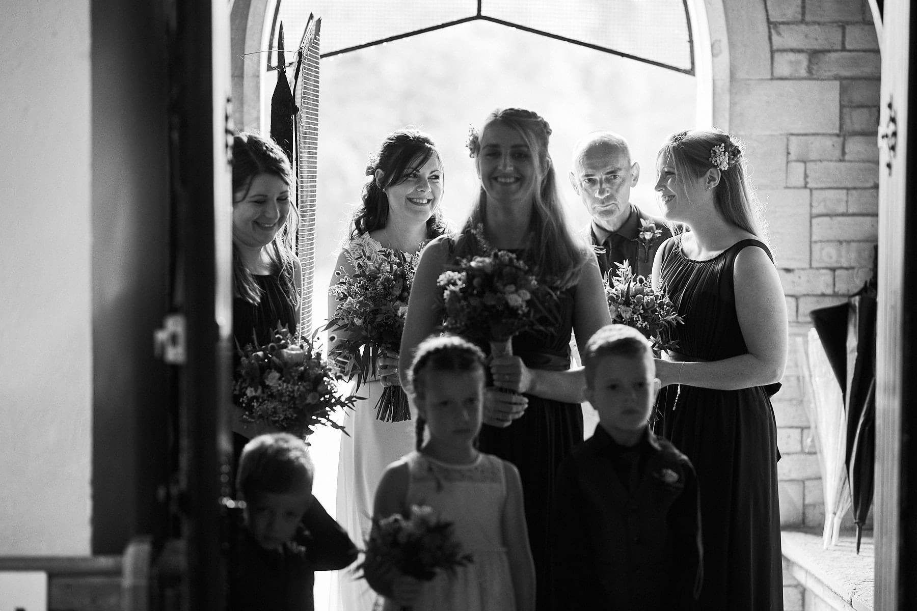 A bride and her party pause in the door of the church on her wedding day at Kirkby on Bain Church