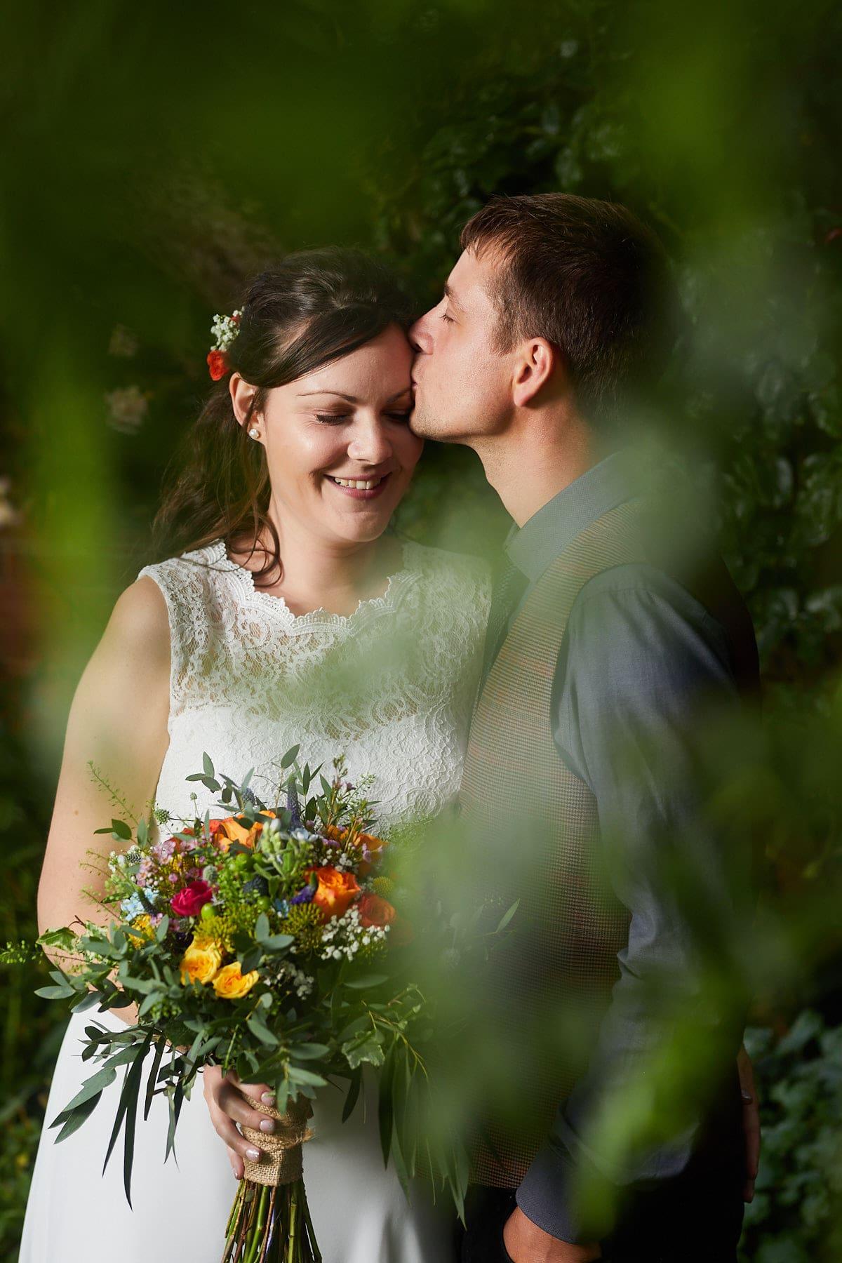 Wedding portrait of a couple kissing through greenery near Woodhall Spa