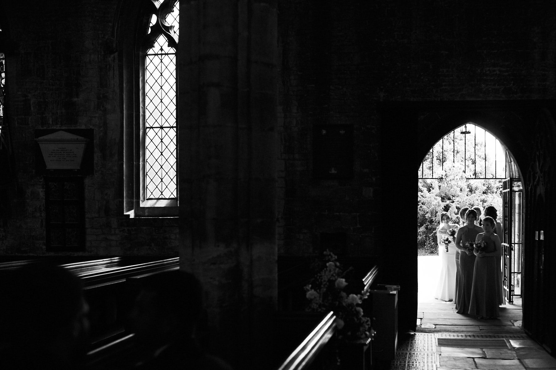 A bride waits in the church doorway on her wedding day