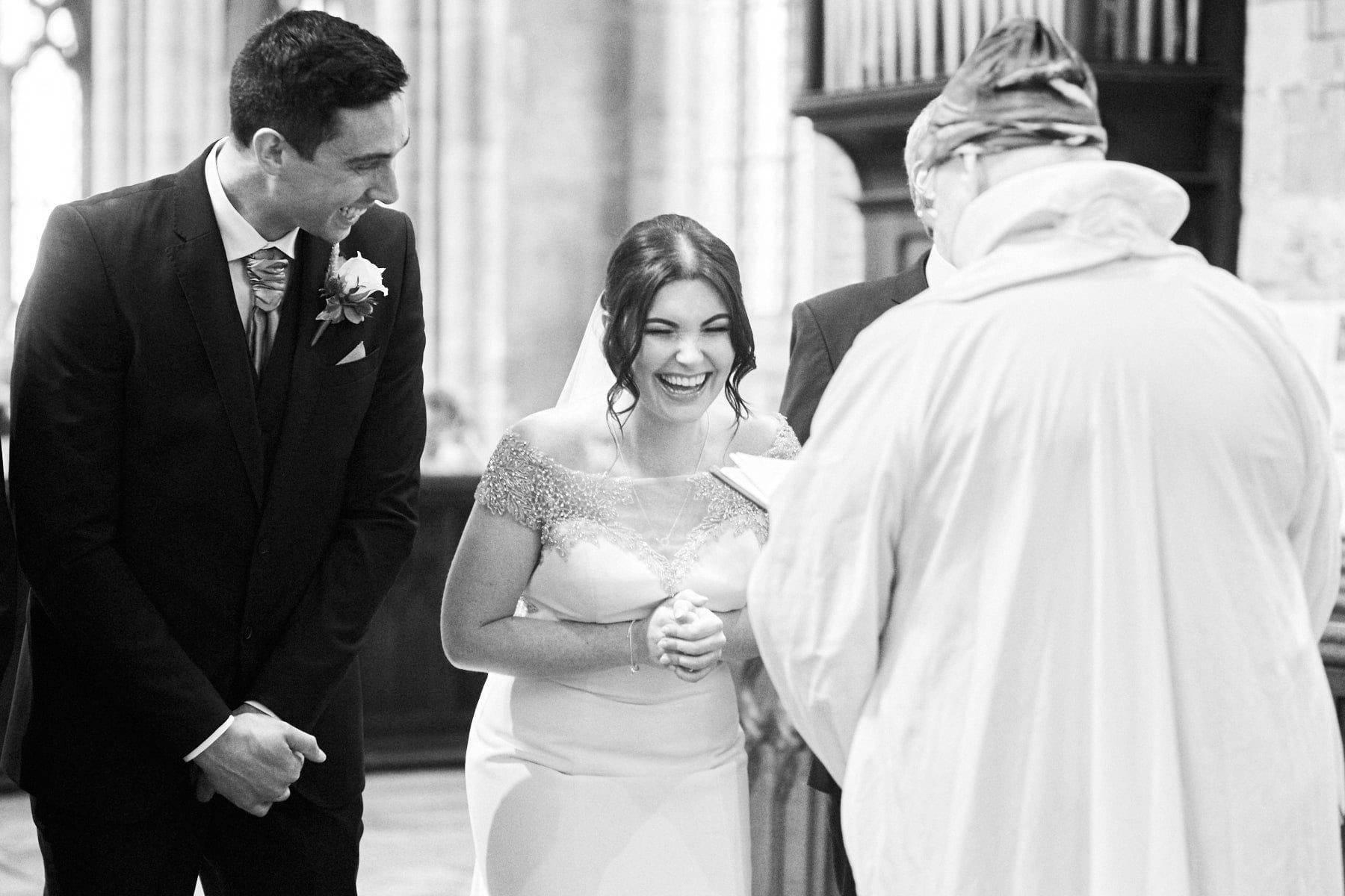 A bride and her groom get the giggles during their wedding ceremony.