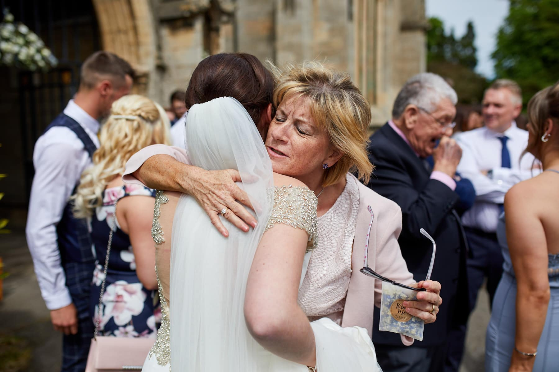 a family member embraces the bride on her wedding day