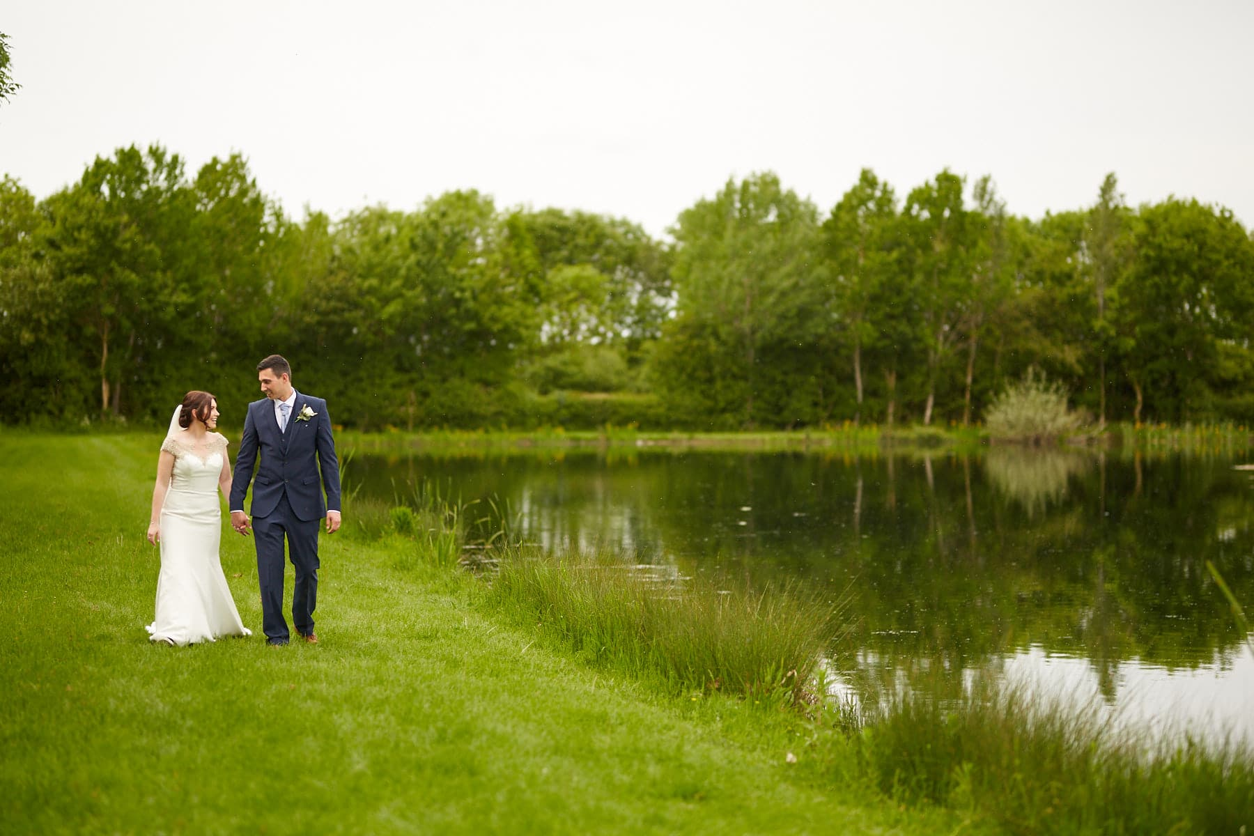 A couple walk by the water on their wedding dayat Howell Manor near Sleaford.