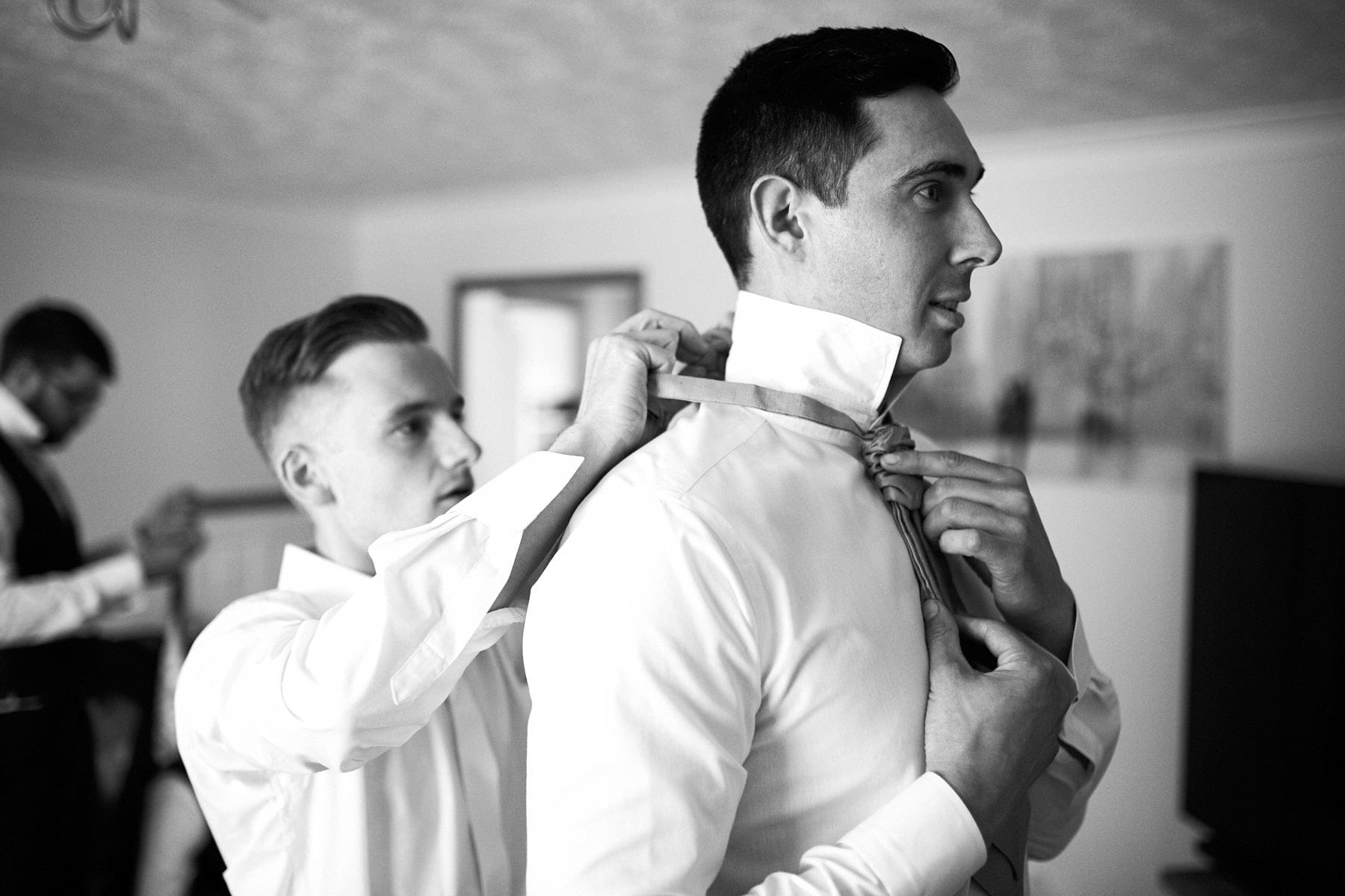 The best man helps the groom adjust his tie on the morning of his wedding.