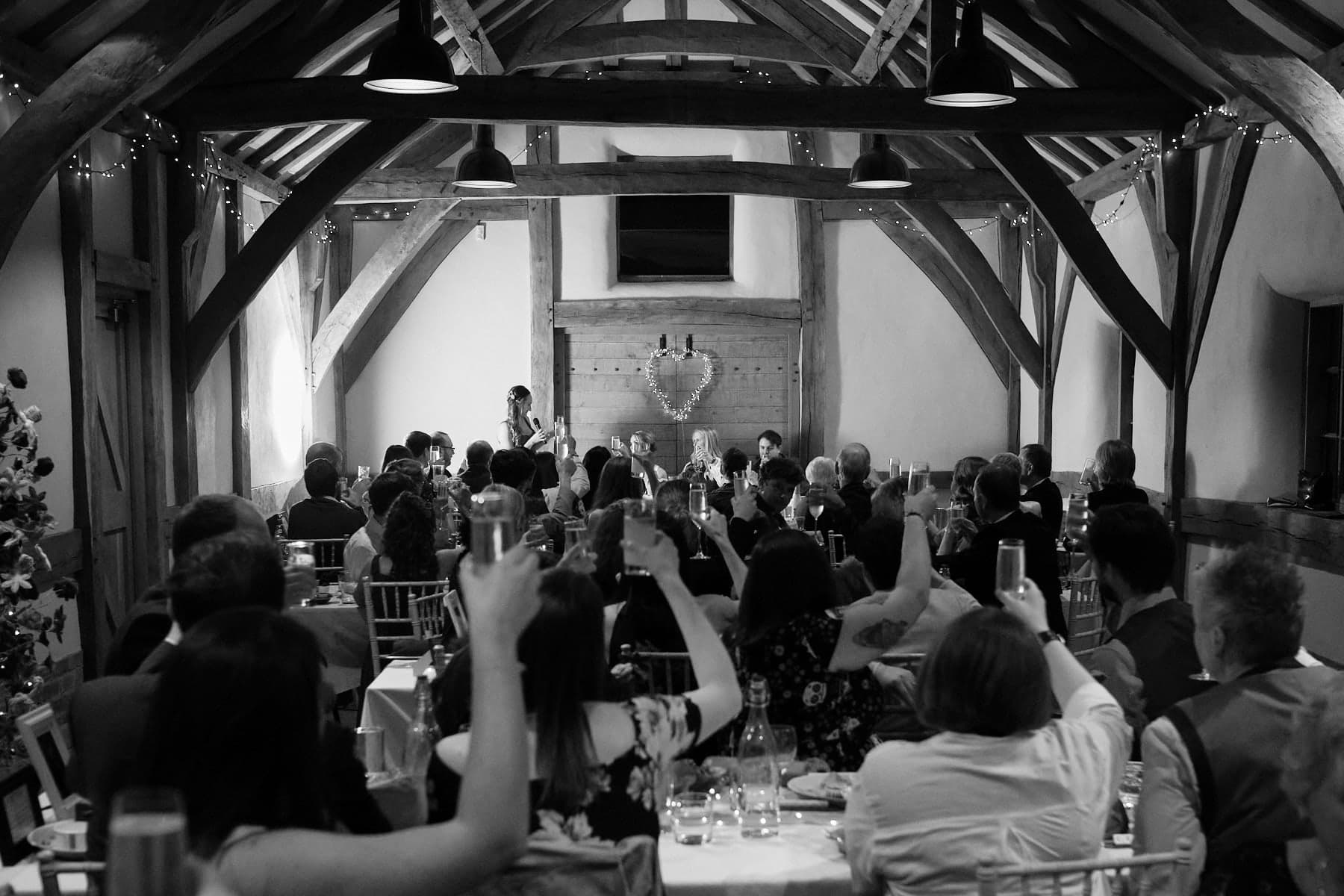 The guests raise a toast during wedding speeches in Woodhall Spa