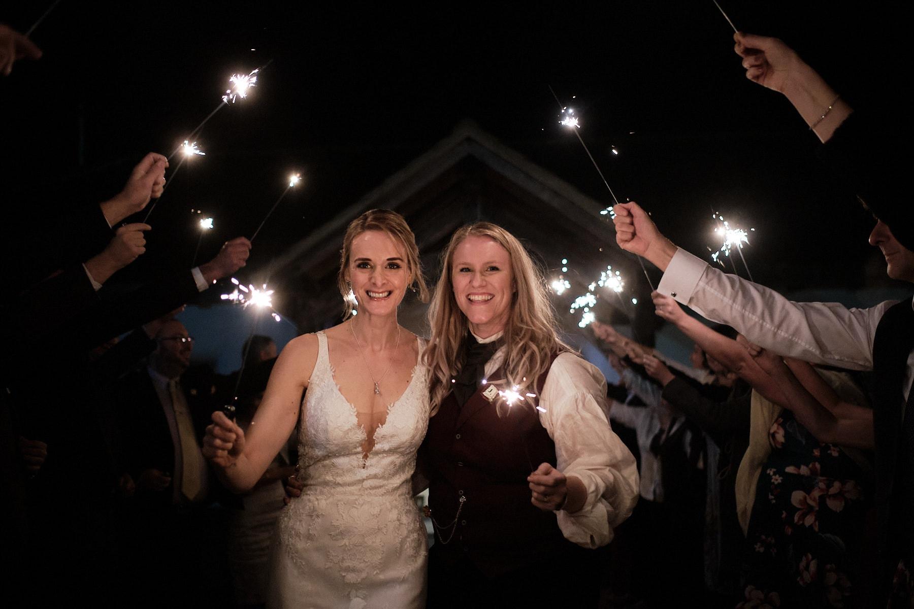 A couple walk through a procession of fireworks on their wedding day in Woodhall Spa at Abbey Farm weddings