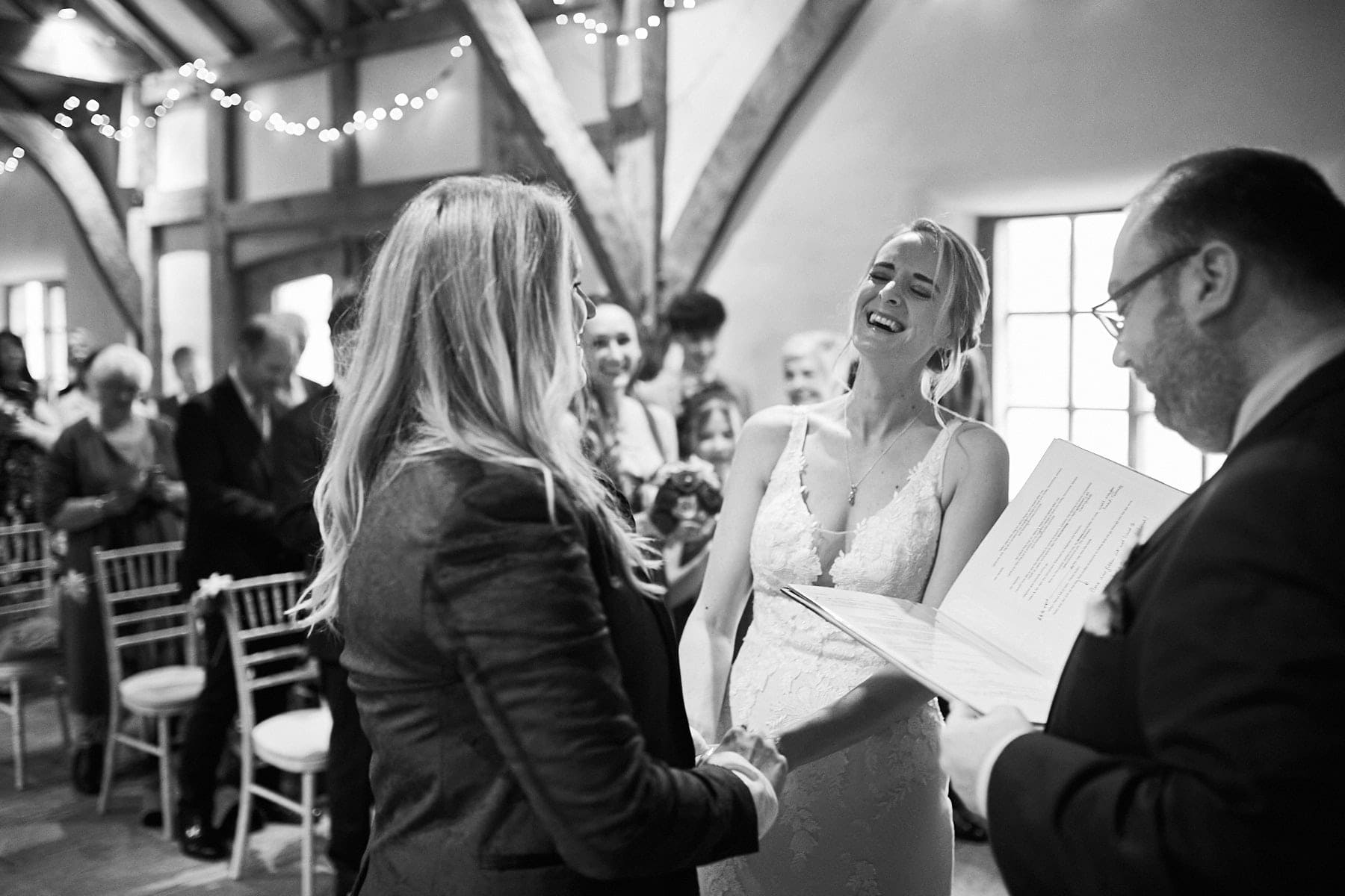 A couple break into laughter on their wedding day during the ceremony