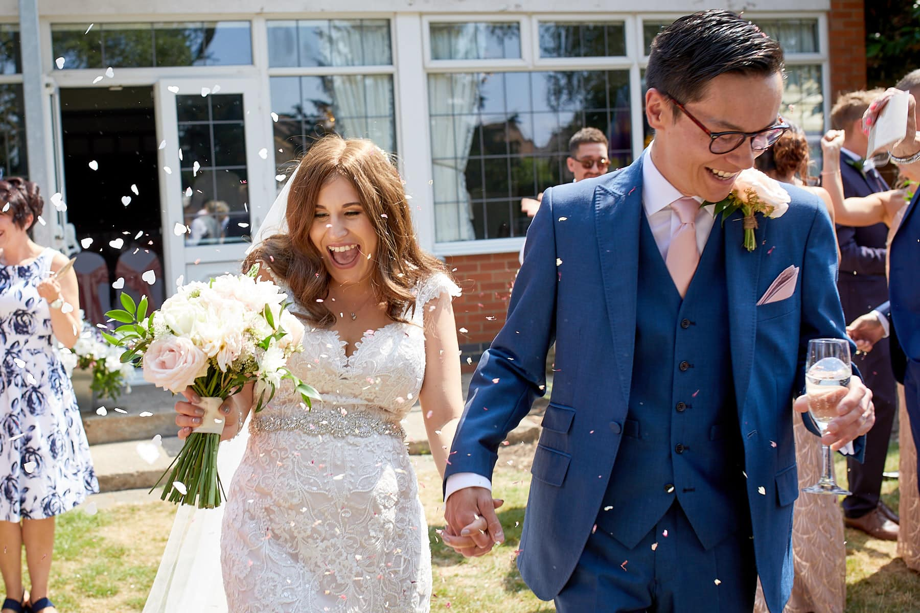 A couple walk through their guests throwing confetti on their wedding day in Skegness