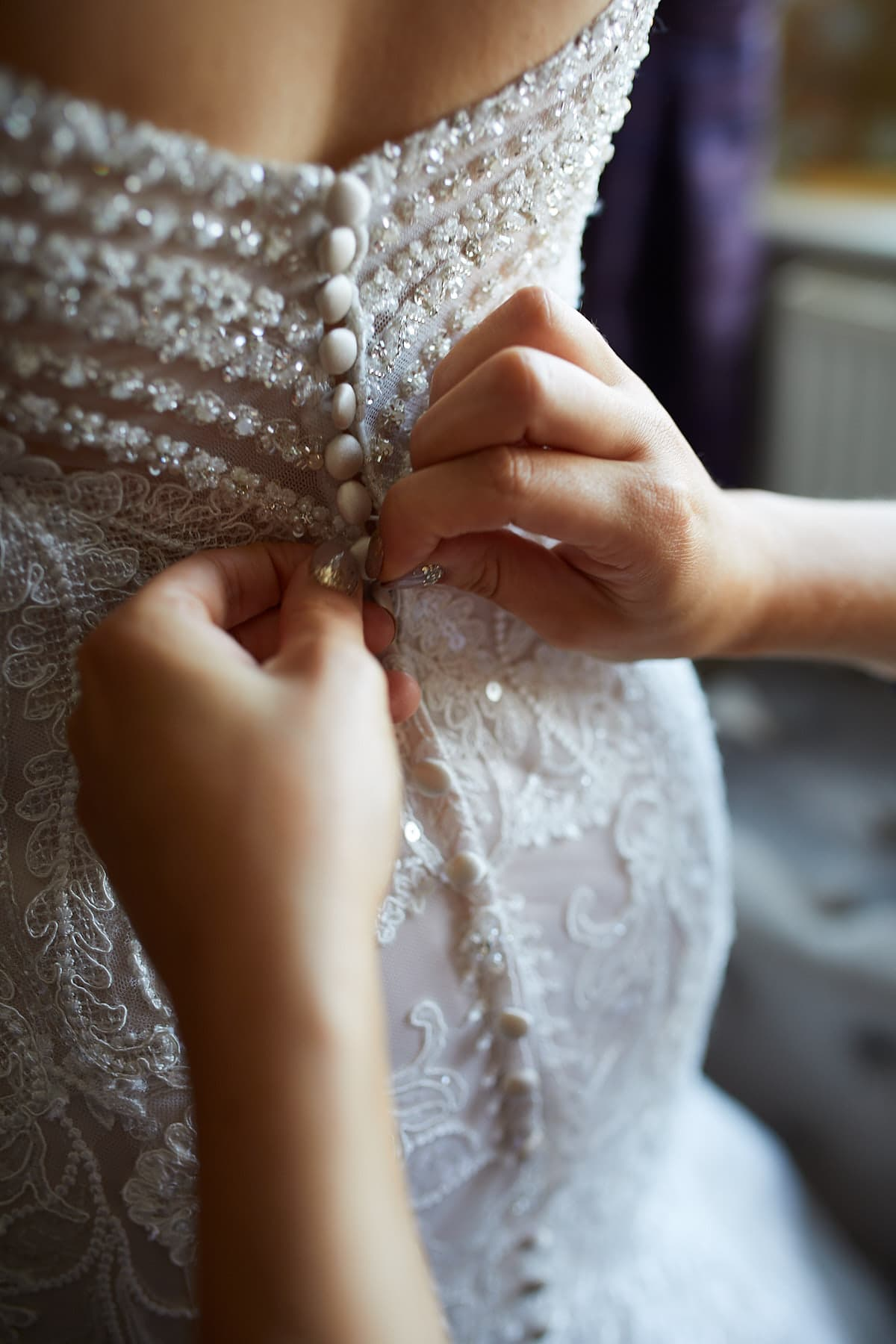 A mother fixes the buttons on her daughters dress during her wedding morning.