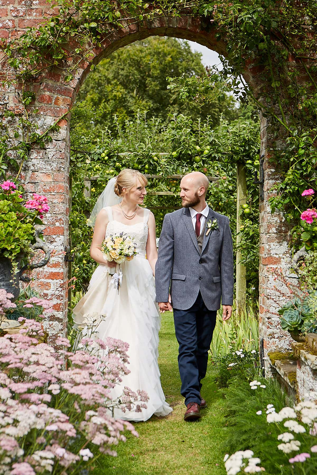 A couple walk through the gardens at Gunby Hall on their wedding day.
