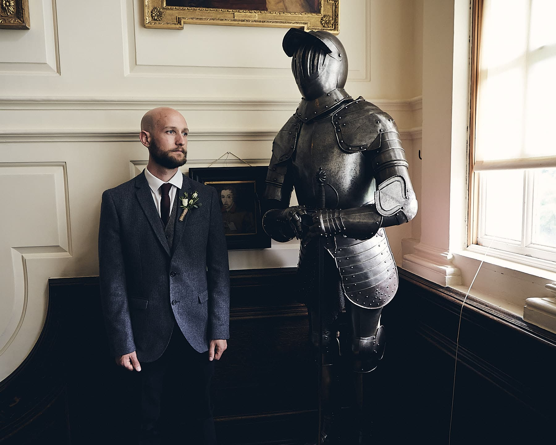 A groom poses by a suit of armour in Gunby Hall Lincolnshire on his wedding day.