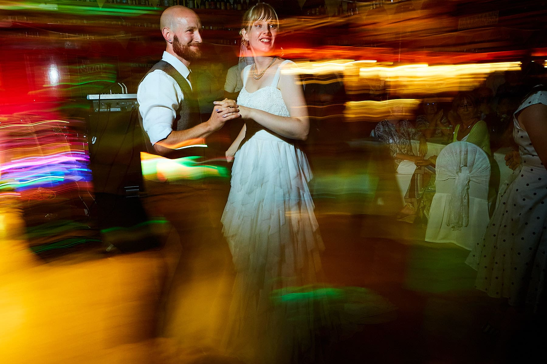 A couple dance on their wedding day agains a slow shutter speed creating a light effect