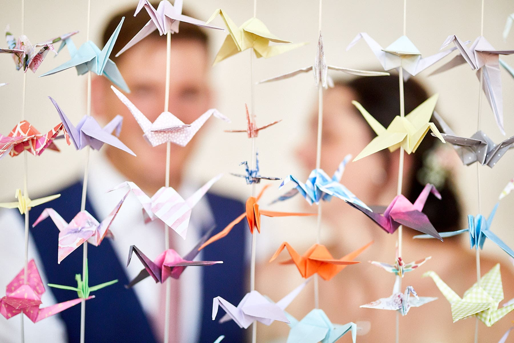a couple pose in front of origami birds on their wedding day in Louth